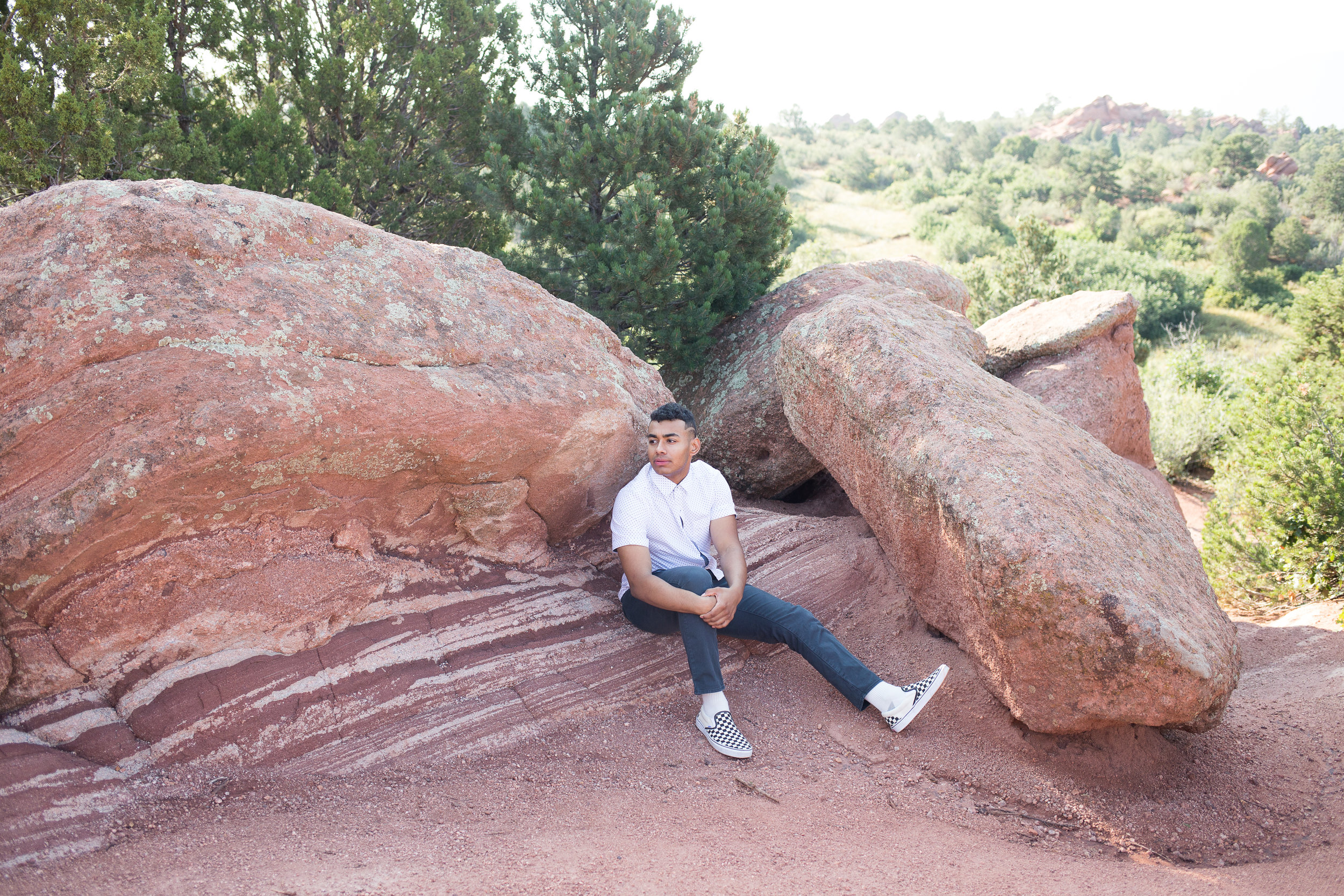 Senior boy looking in the distance while sitting on red rocks in Garden of the Gods for senior photos, Stacy Carosa Photography