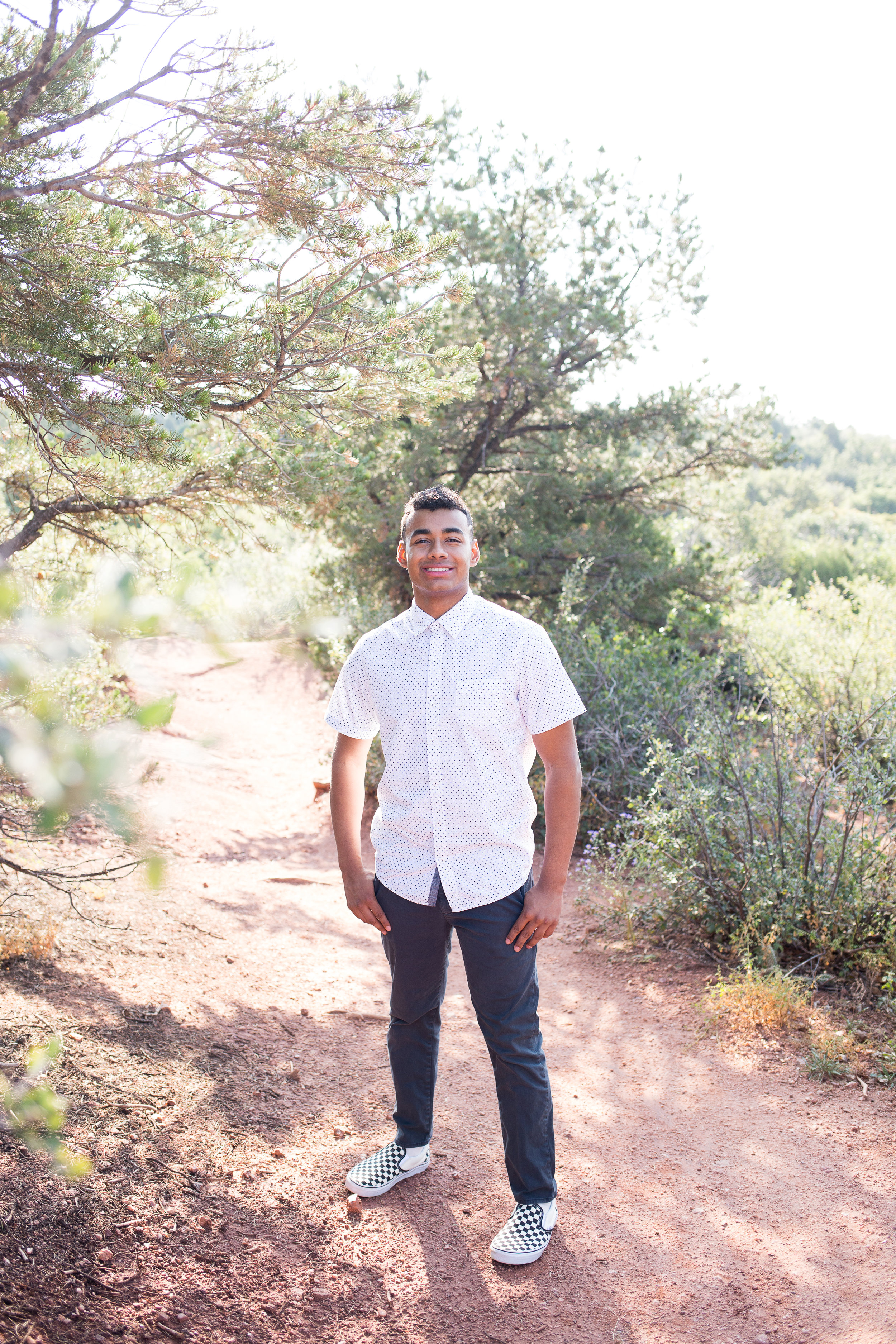 High s chool senior boy standing amount the trees in Garden of the Gods for his Liberty High School senior photos, Stacy Carosa Photgraphy