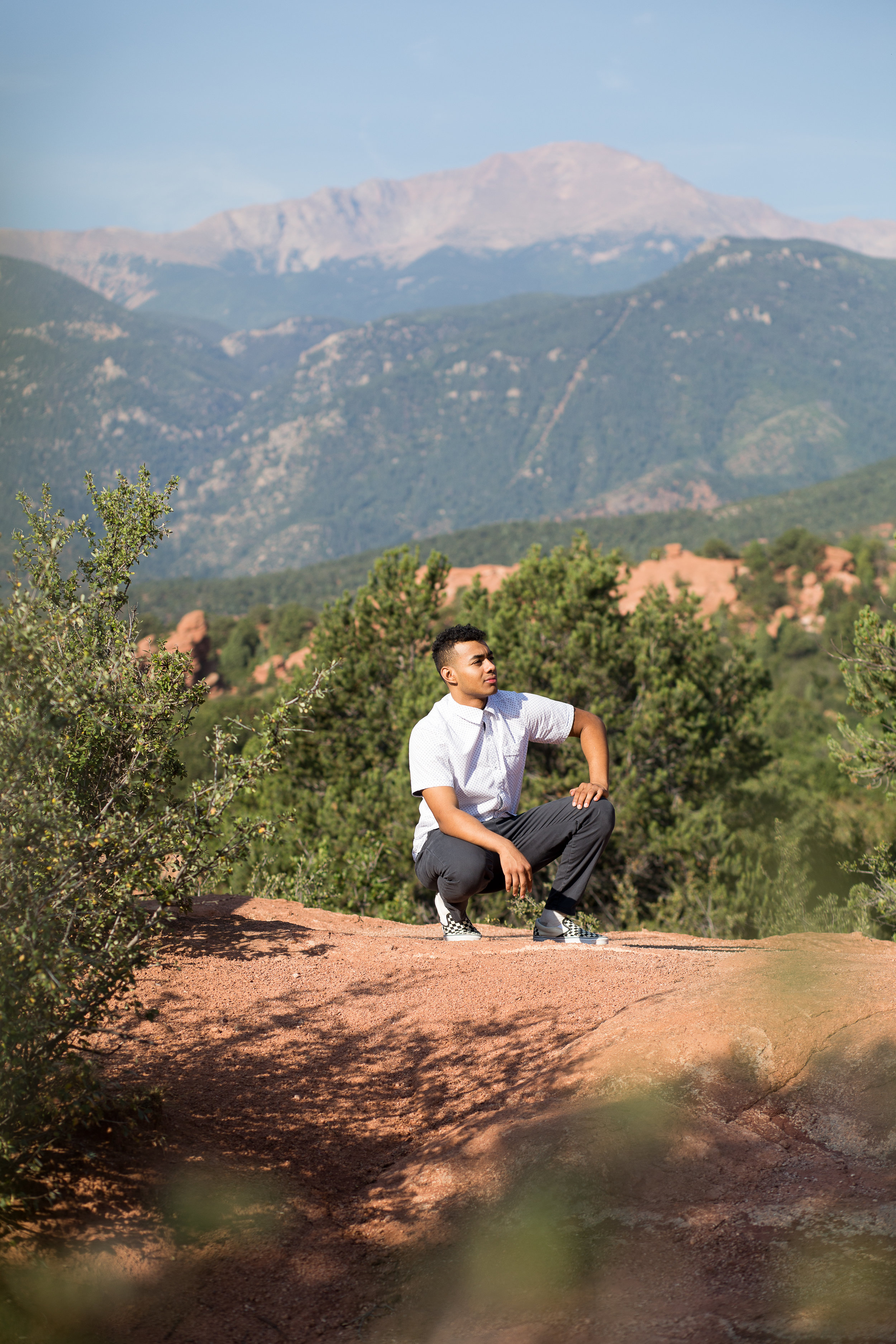 Liberty High School senior kneeling on rocks in front of Pikes Peak in Garden of the Gods looking in the distance Stacy Carosa Photography