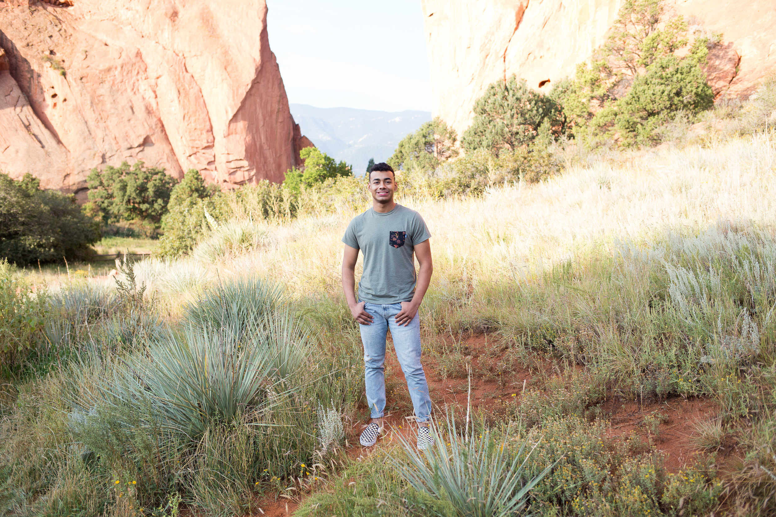 senior boy standing in front of the Garden of the Gods red rocks scenery or senior pictures, Stacy Carosa Photography