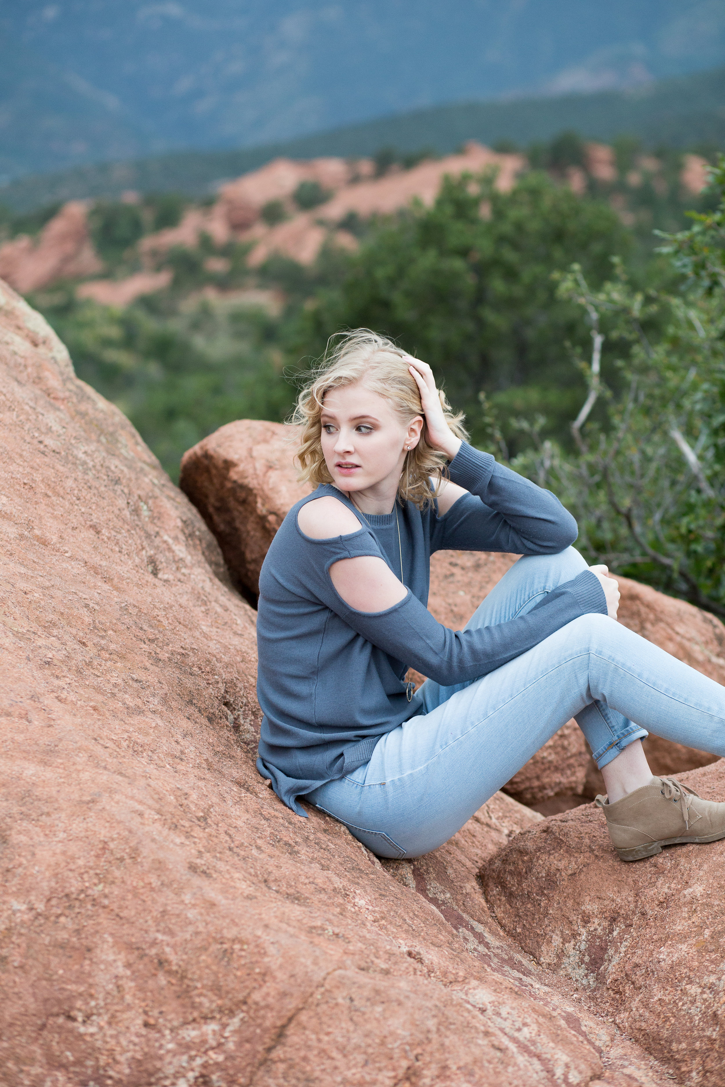 Girl sitting on red rock in Garden of the God with hand in hair and looking behind her, Colorado Springs, Stacy Carosa Photography Senior Session