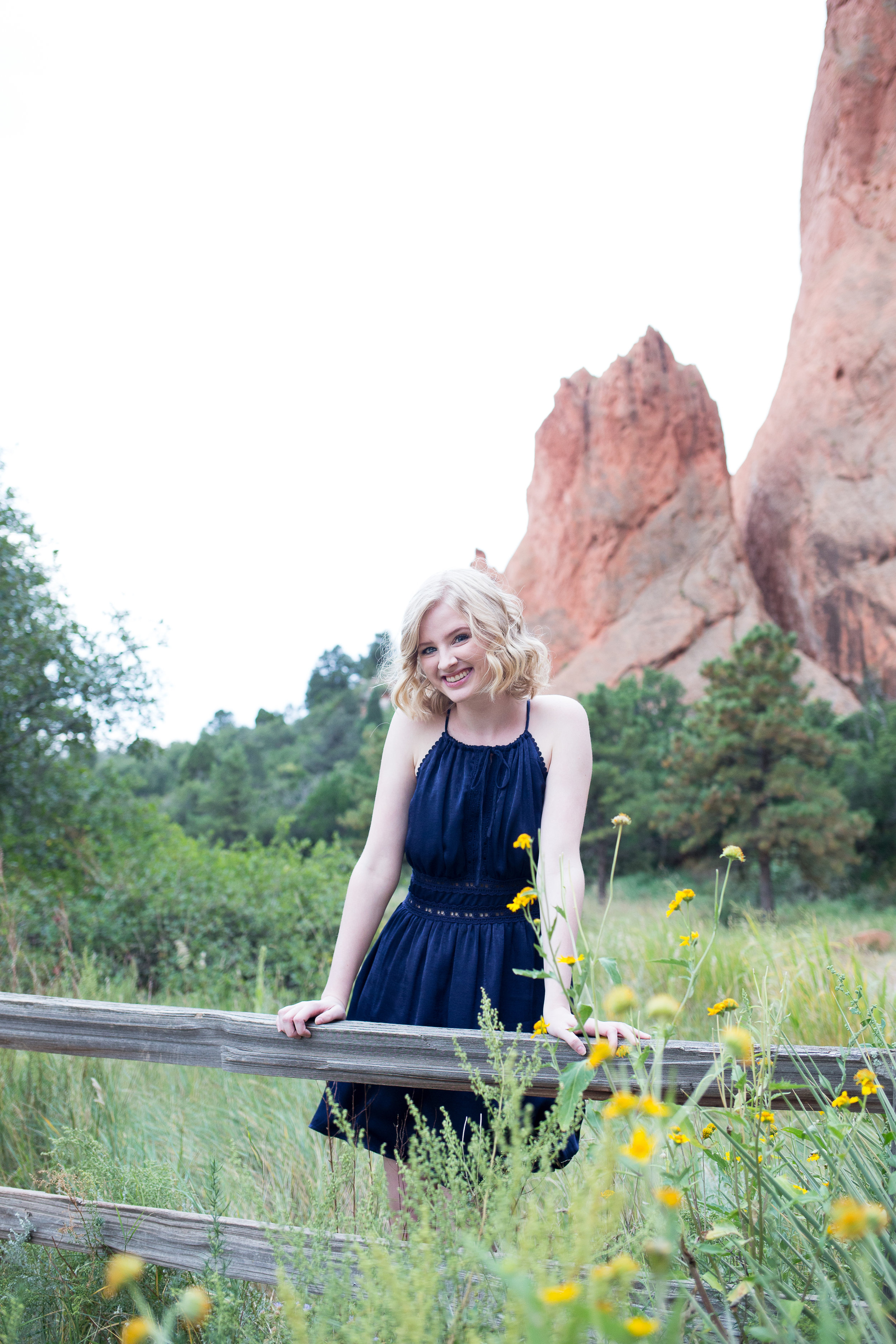Girl standing among the tall grasses outside for her senior photos in  Garden of the Gods, Stacy Carosa Photography