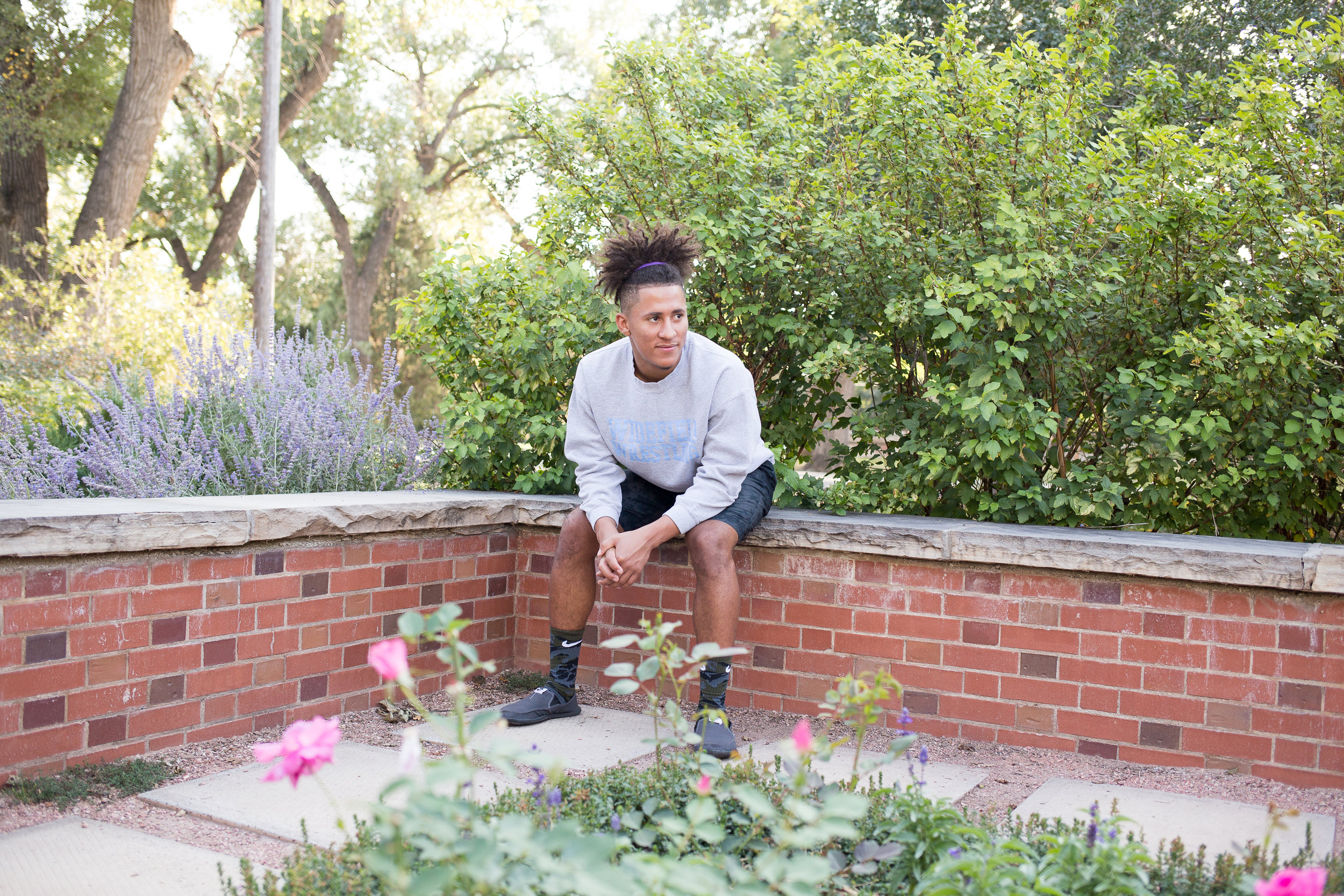 Senior male sitting on a brick wall among flowers at Monument Valley Park looking in the distance for senior photos. Stacy Carosa Photography. Widefield High Colorado Springs Senior Photography