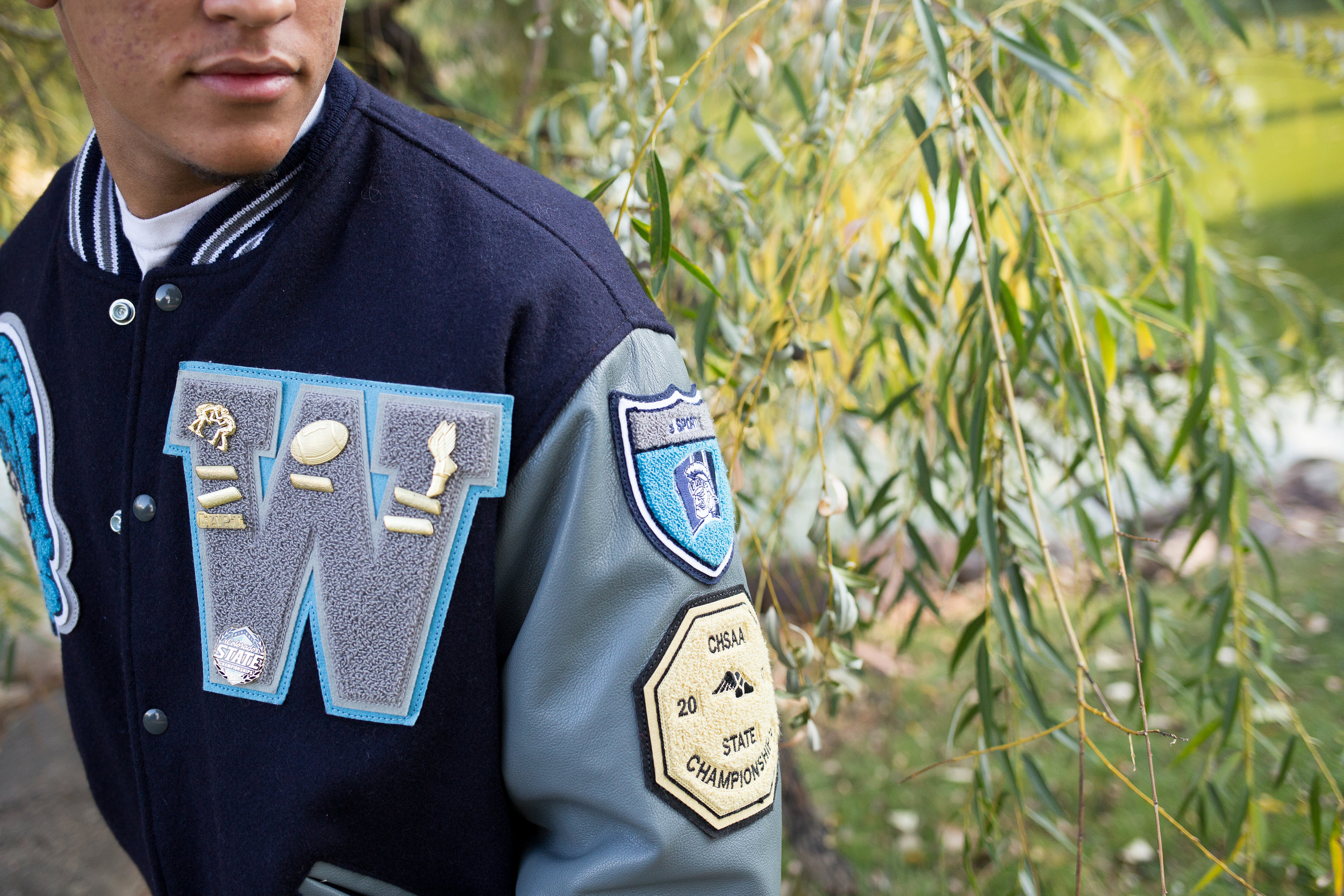 Widefield High School senior photos of varsity jacket close up at Monument Valley Park in Colorado  Springs Stacy Carosa Photography