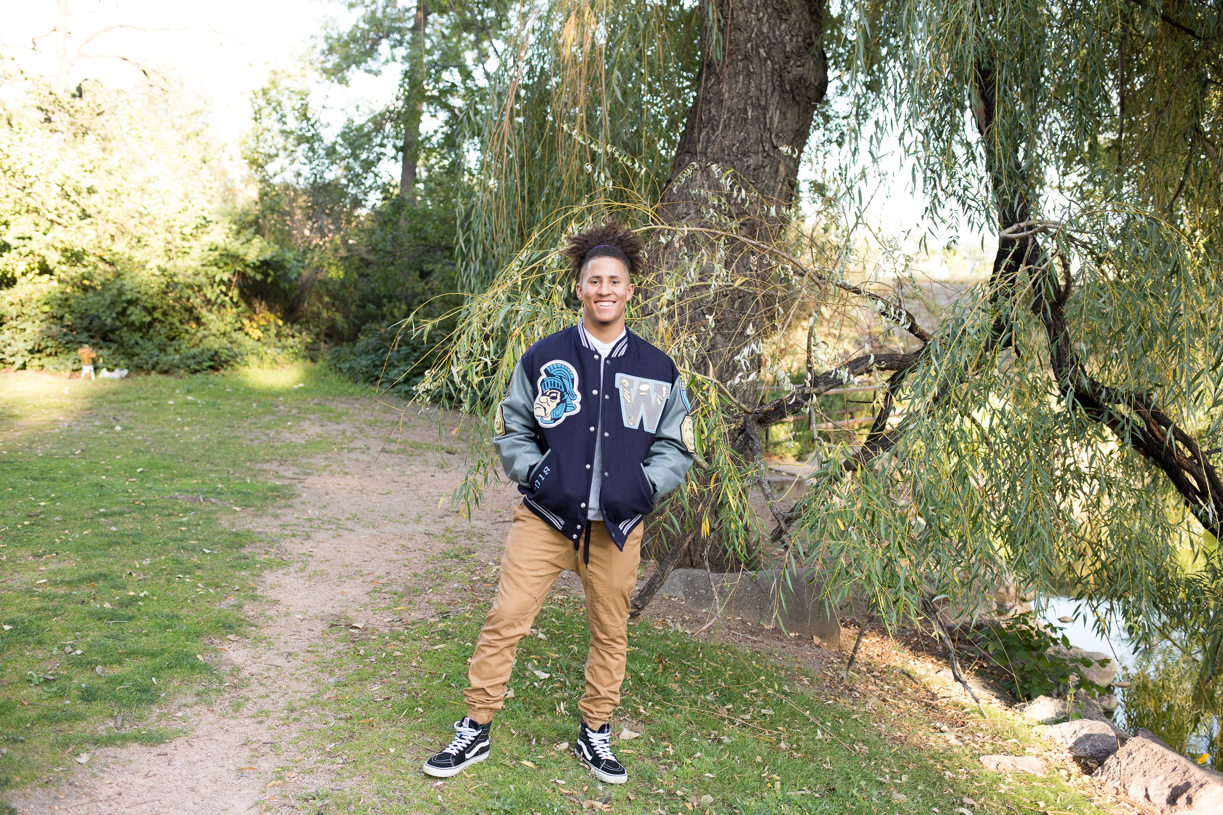 Colorado  Springs Senior Photography Senior standing near trees and pond in Monument Valley Park in his varsity jacket for Widefield High School Stacy Carosa Photography