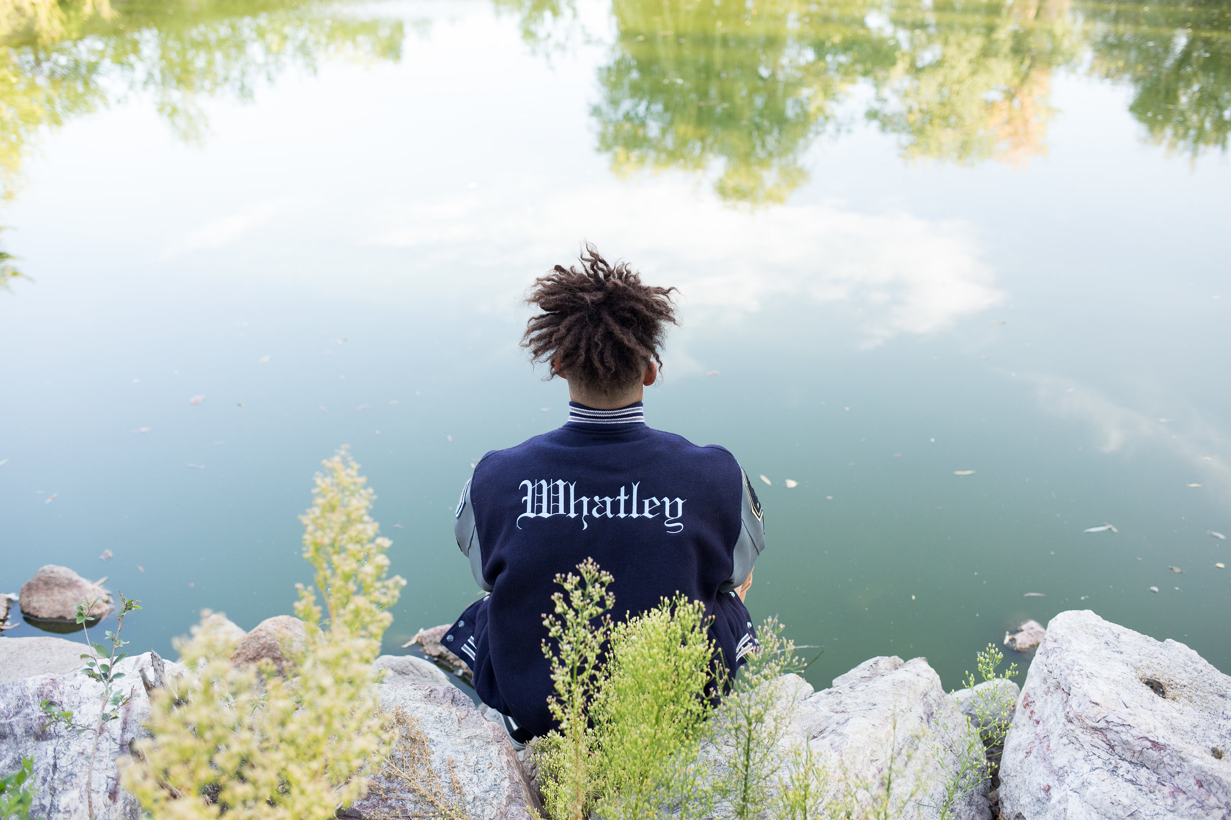 Senior sitting by pond and looking at the water with the back of his varsity jacket facing the camera in Monument Valley Park Stacy Carosa Photography Colorado Springs