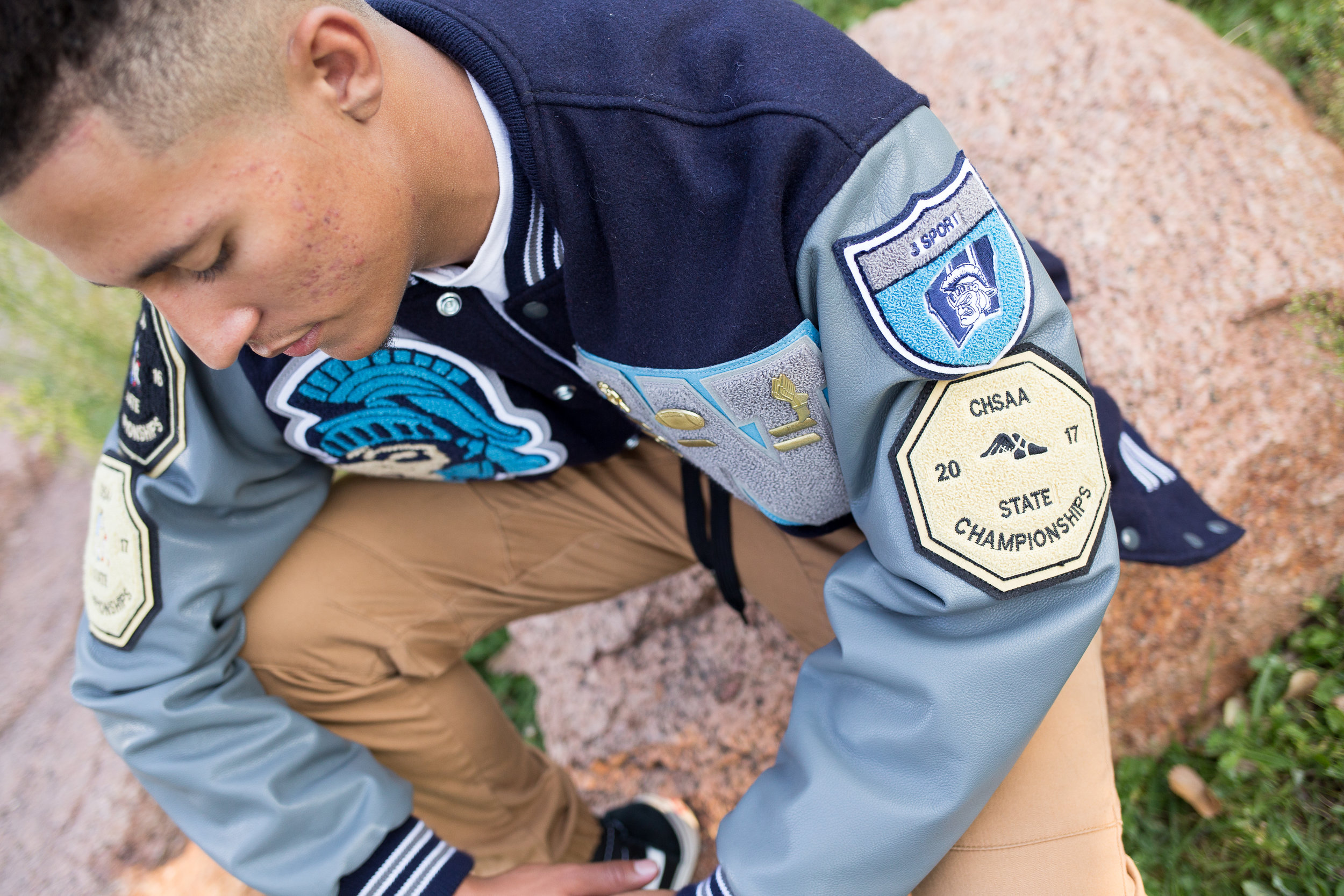 Colorado Springs senior photography in Monument Valley Park with a close up of the badges on the varsity jacket for Widefield High School Stacy Carosa Photography