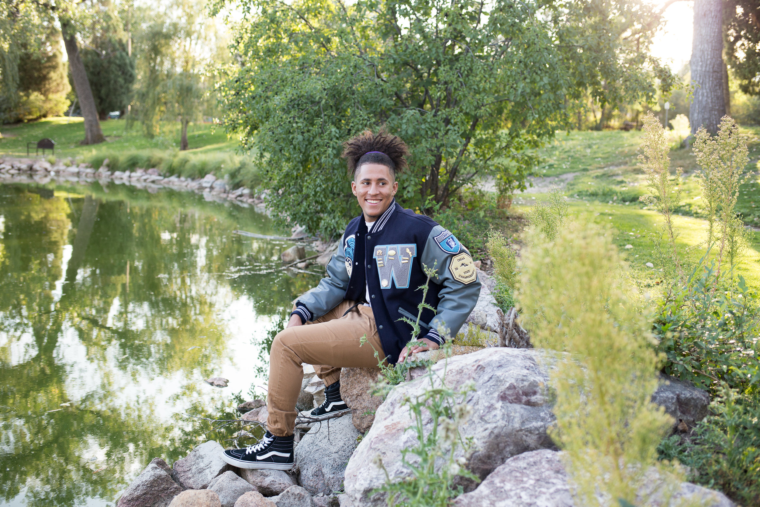 senior sitting on a rock in Monument Valley Park by the pond and turning to look at the camera Colorado Springs senior photography in Colorado Springs Stacy Carosa Photography