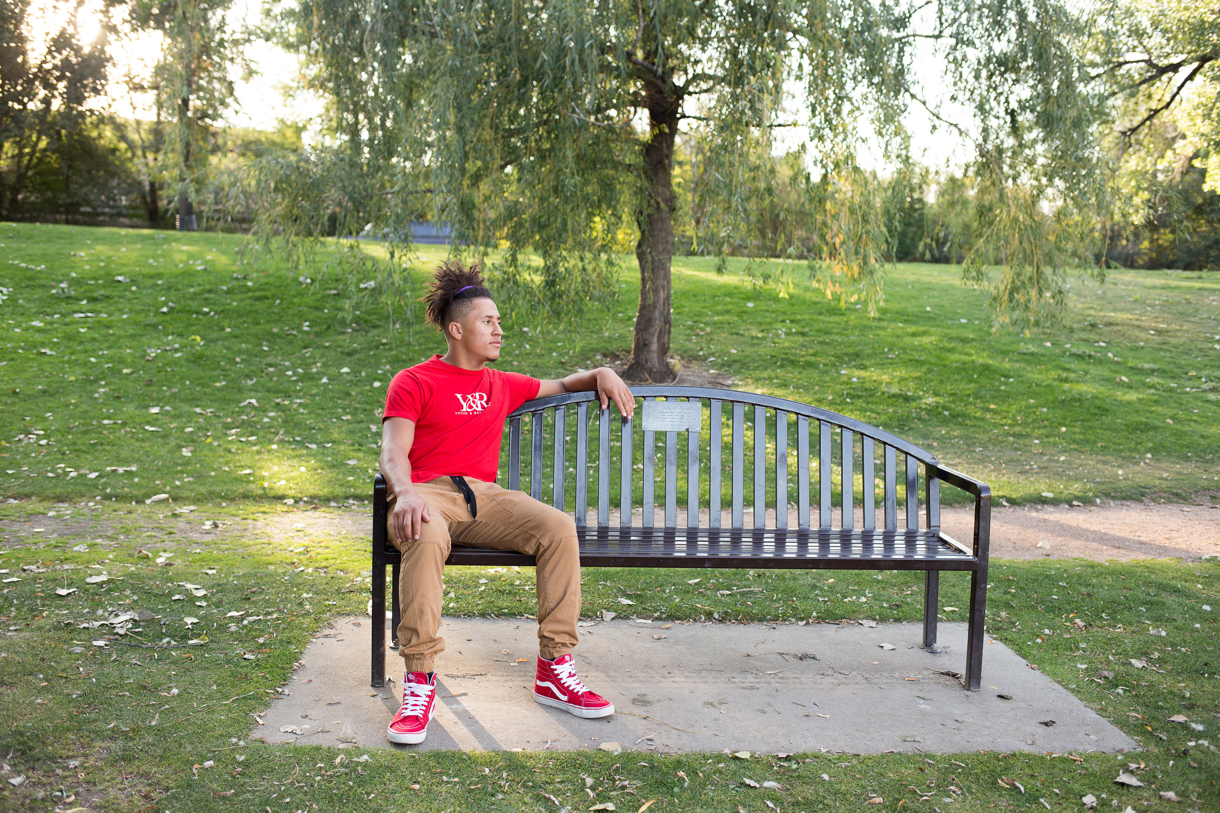 Senior sitting on the left side of a bench while looking in the distance in a red shirt in Monument Valley Park in Colorado  Springs Stacy Carosa Photography class of 2019