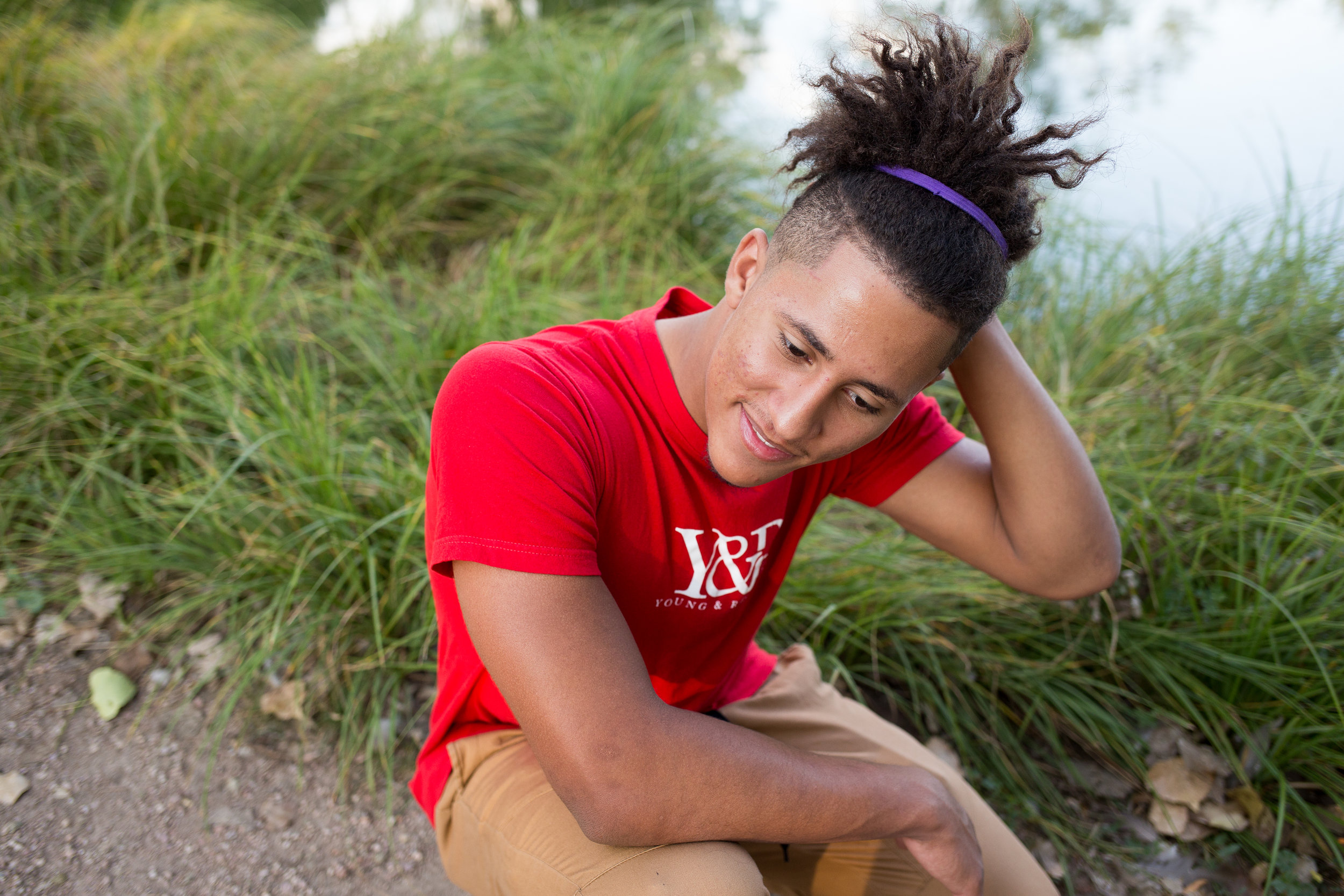 Senior boy in red shirt kneeling and looking at the ground while running his hand through his hair in Monument valley Park Stacy Carosa Photography Colorado Springs Senior Photography