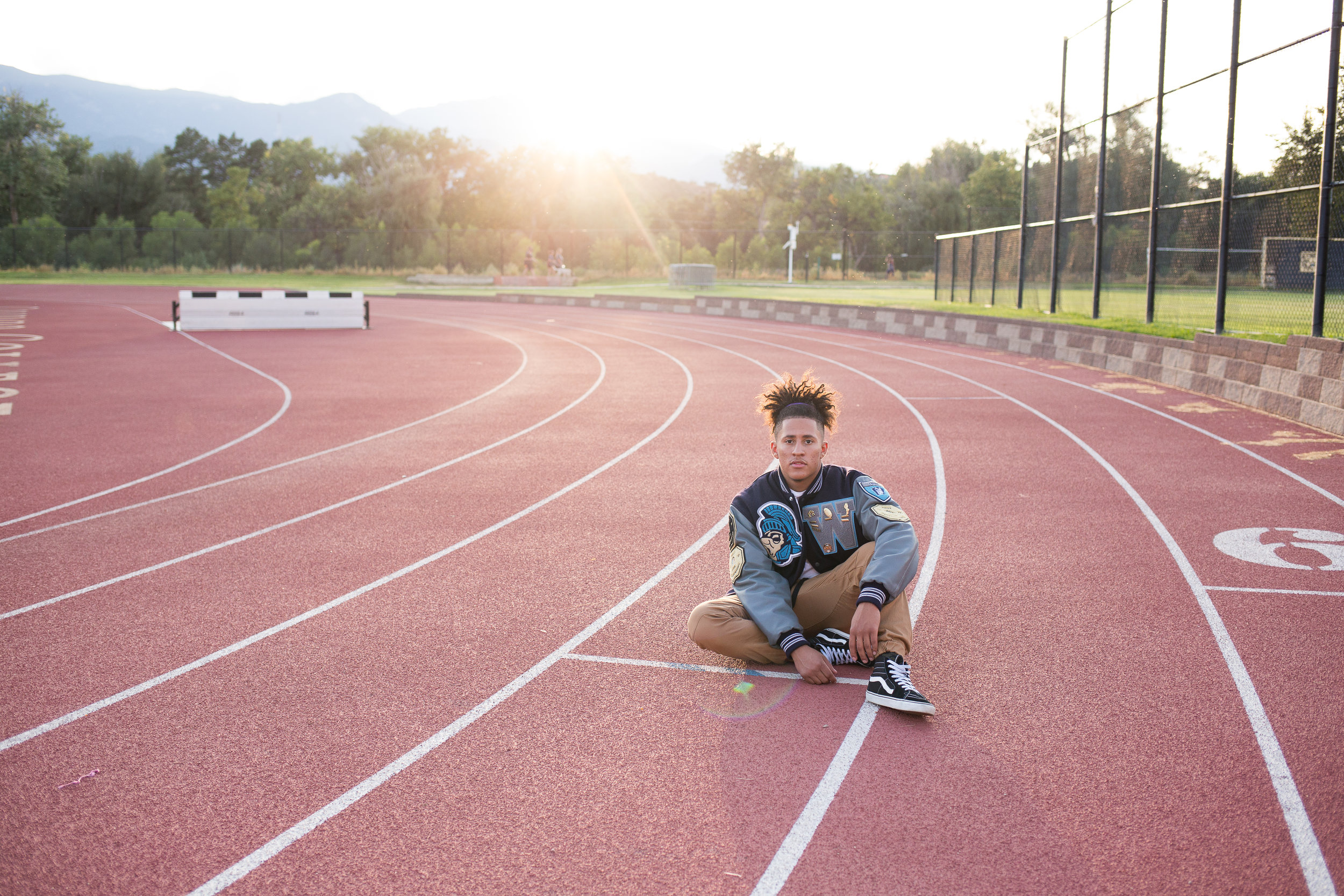 Widefield High School senior in varsity jacket sitting on a track at Colorado College for his Colorado Springs Senior Photos Stacy Carosa Photography