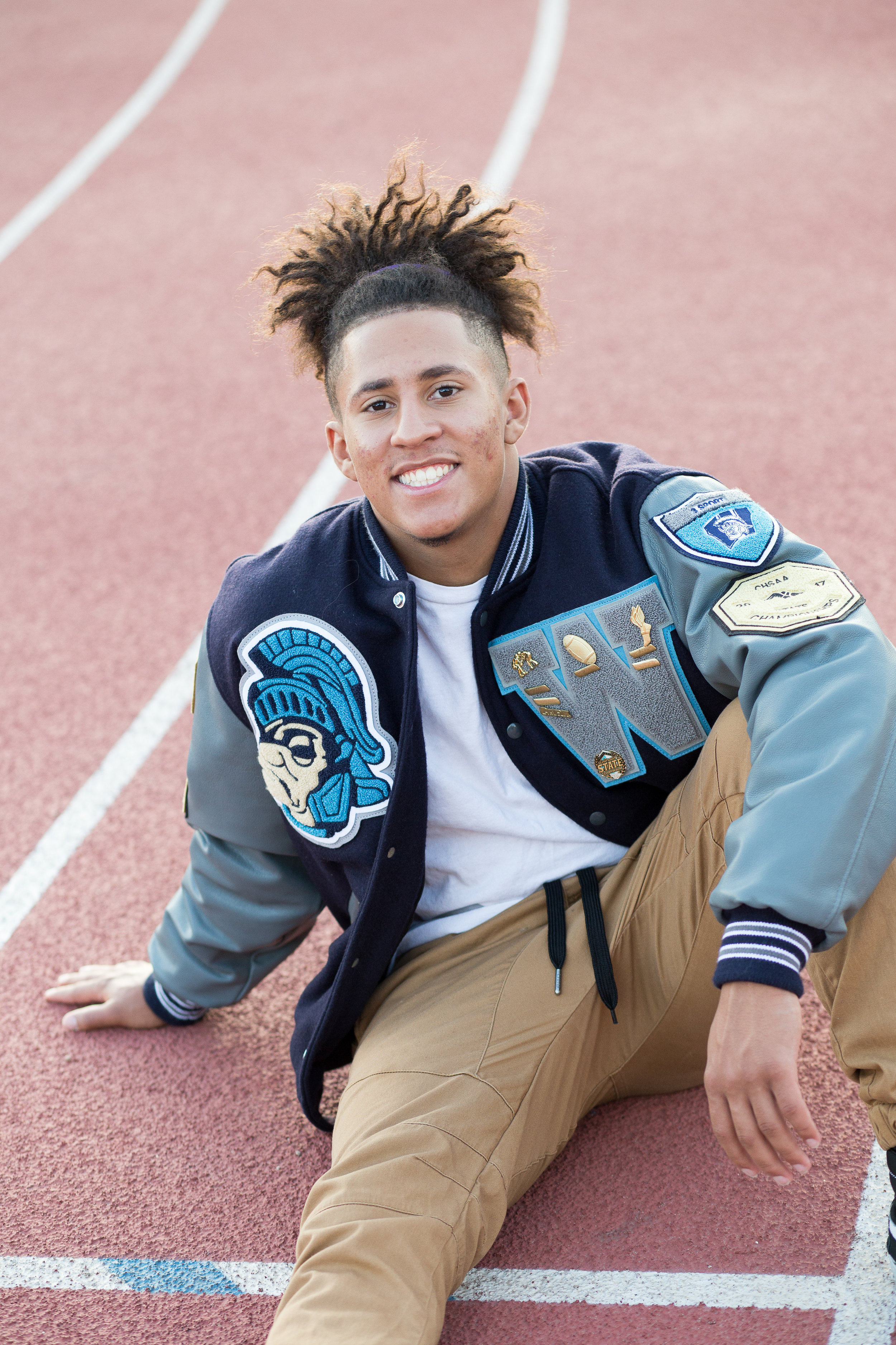 Senior in varsity jacket sitting on a track leaning back on hand smiling at camera Stacy Carosa Photography Colorado Springs
