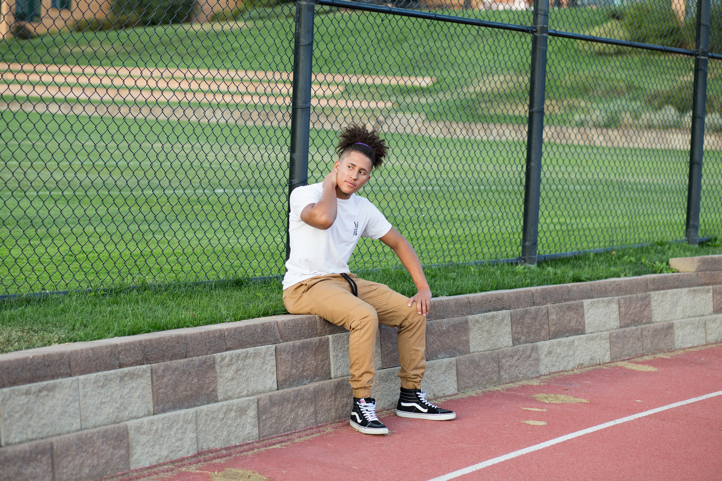 Boy sitting on a stone wall and rubbing neck next to a track in Colorado  Springs Stacy Carosa Photography