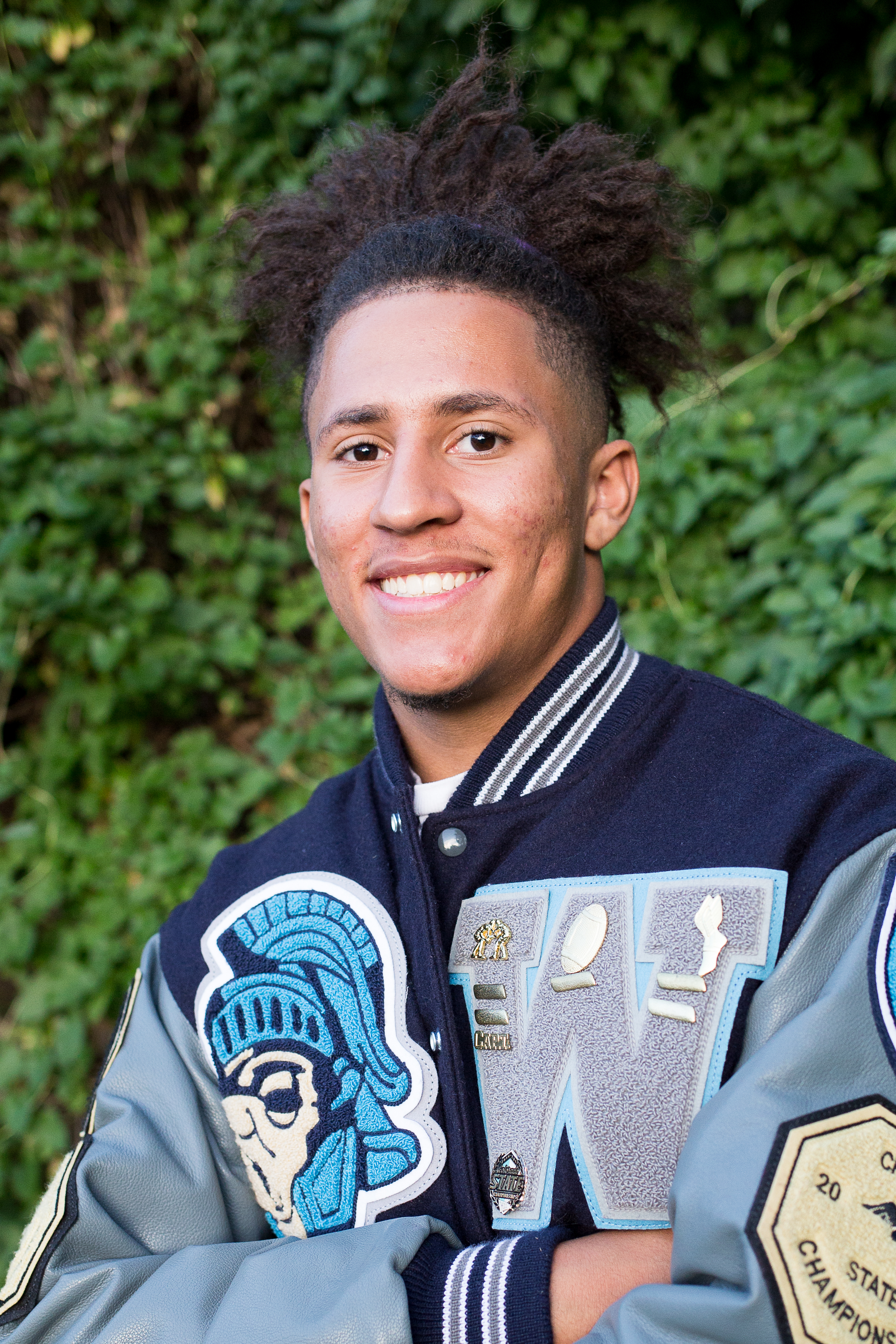 Head shot of a Widefield High School senior in  their varsity jacket in front of a green wall smiling Stacy Carosa Photgraphy Colorado Springs senior photos