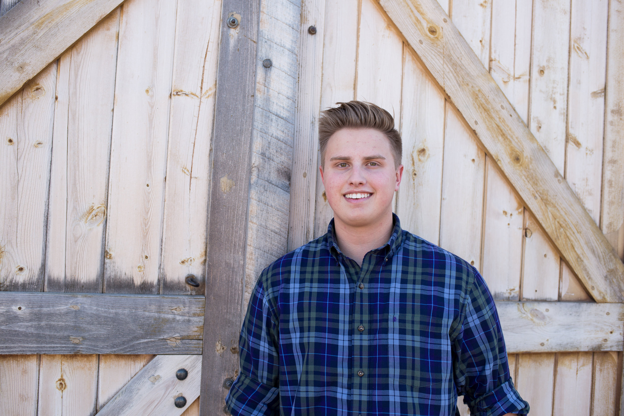 St. Mary's Senior Photos at Rock Ledge Ranch leaning against a barn door in a flannel shirt Stacy Carosa Photography Colorado Springs