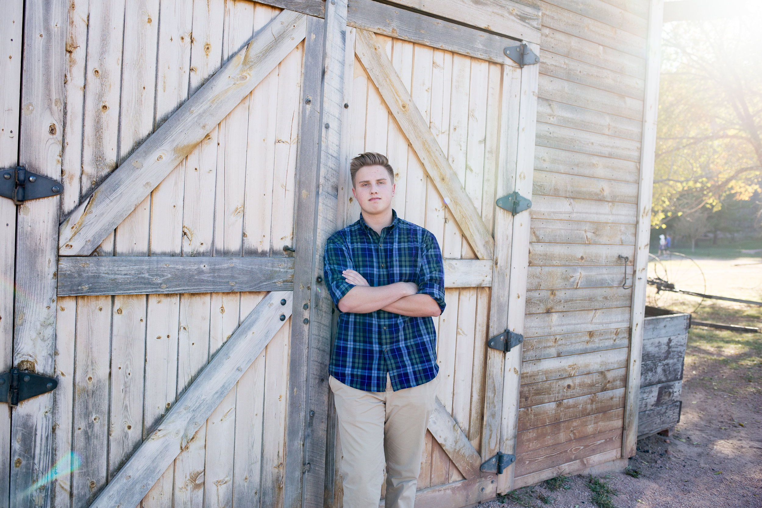 Senior boy leaning against barn door with arms crossed at Rock Ledge Ranch for senior photo session Stacy Carosa Photography Colorado Springs seniors