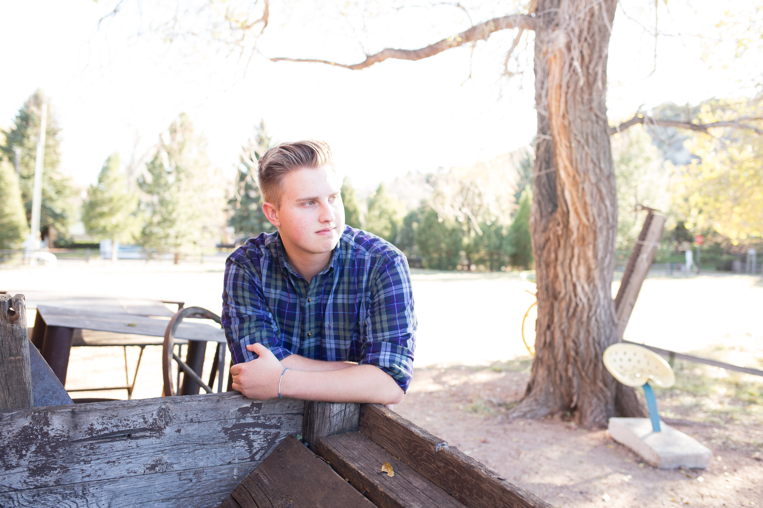 Senior leaning against crate at Rock Ledge Ranch with sunlight on his face and looking in distance Stacy Carosa Photography Colorado Springns Rock Ledge Ranch