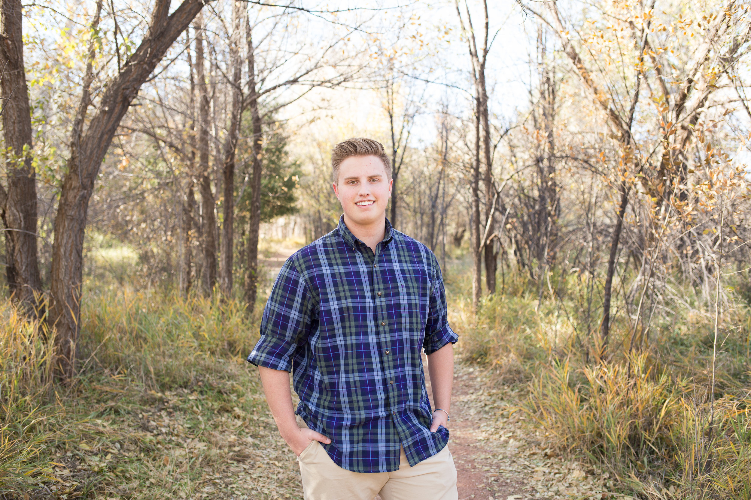 During a senior session boy standing on path among the trees at Rock Ledge Ranch Colorado Springs Stacy Carosa Photography