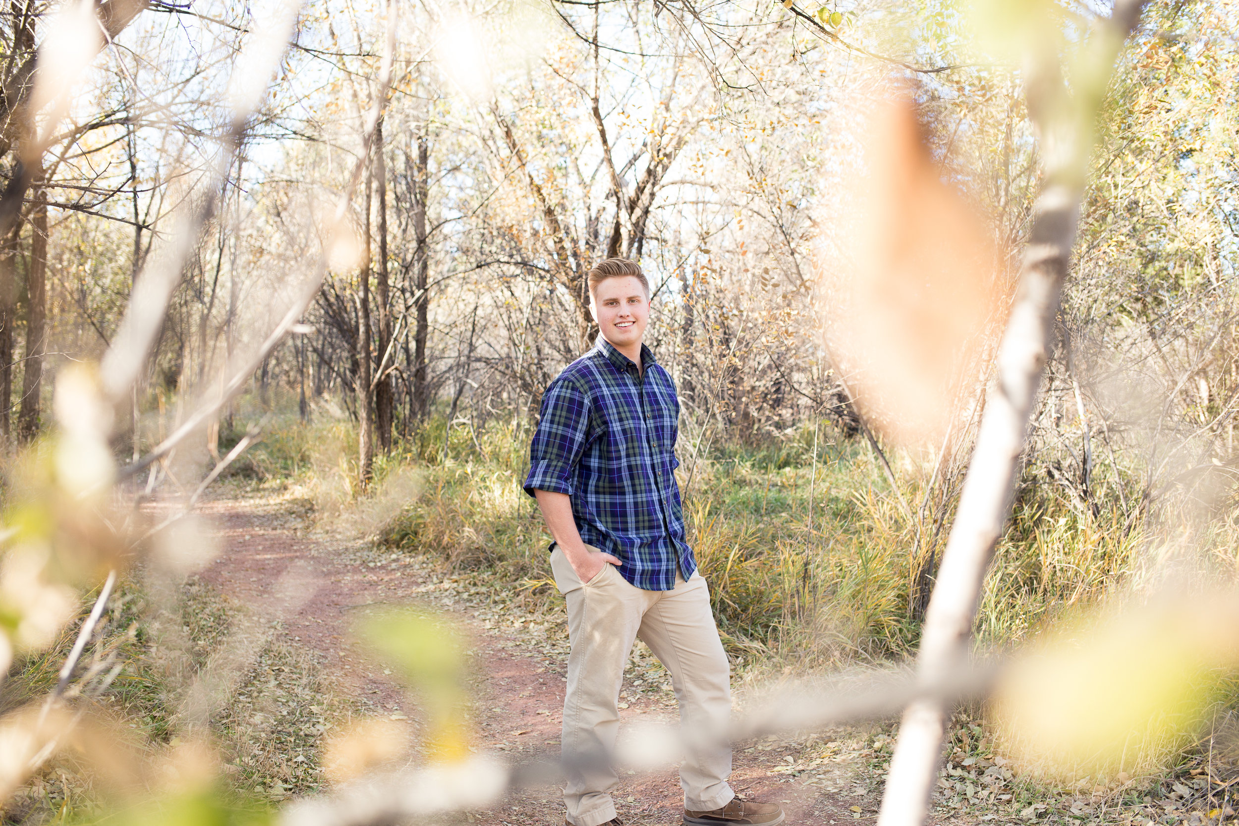 With leaves in the foreground senior boy standing on path with hands in pockets at Rock Ledge Ranch Colorado  Springs Stacy Carosa Photography