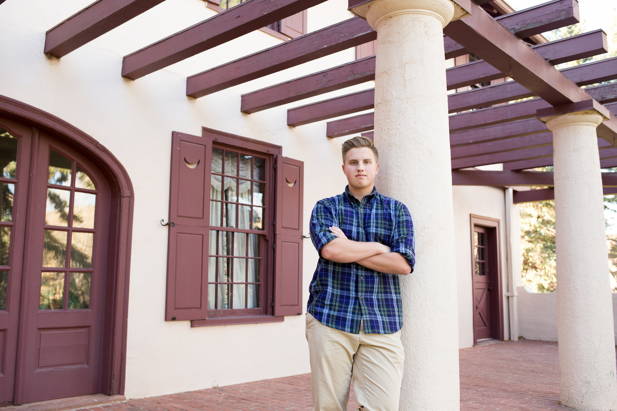 Rock Ledge Ranch Senior Session boy standing and leaning on pillar of a house with arms crossed looking at camera Stacy Carosa Photography