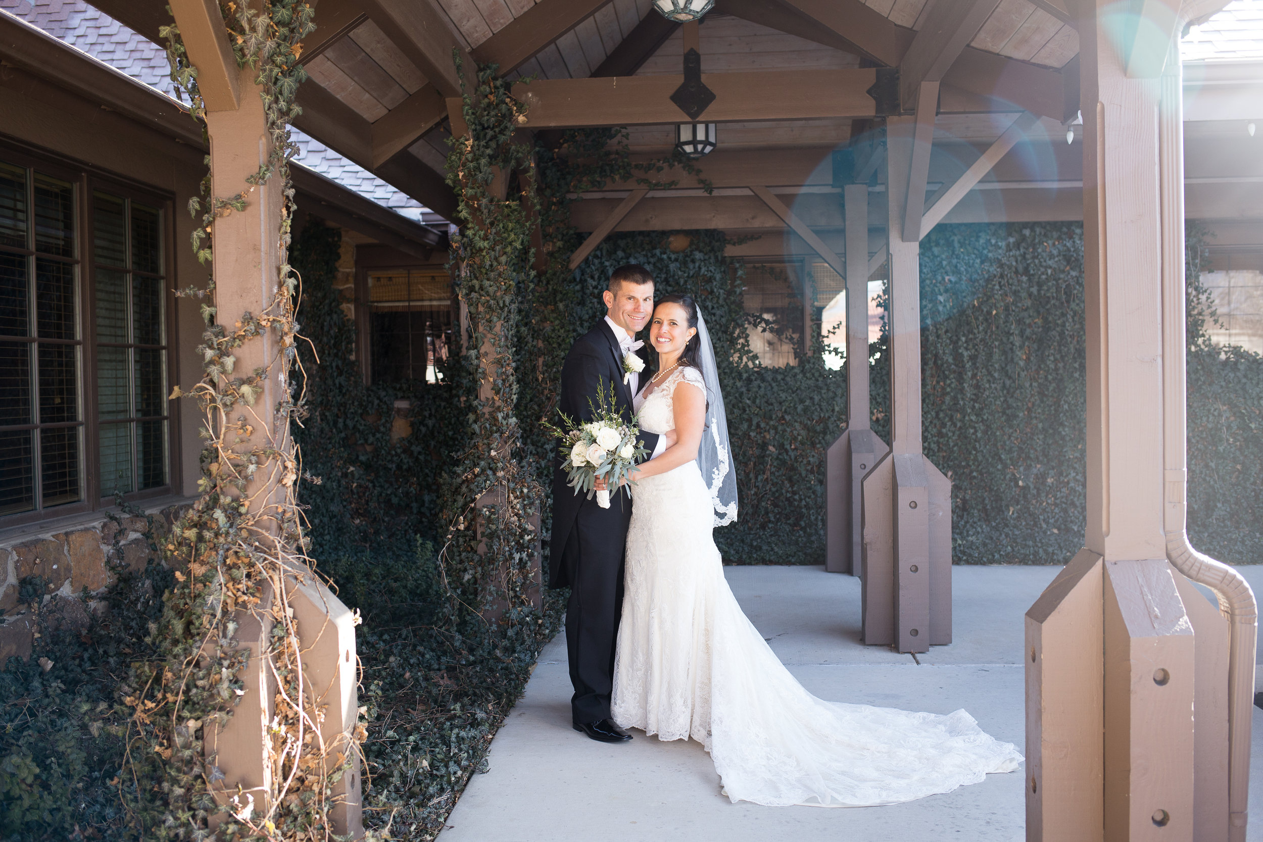 Winter wedding with couple standing under entryway to Colorado Springs Country Club Stacy Carosa Photography