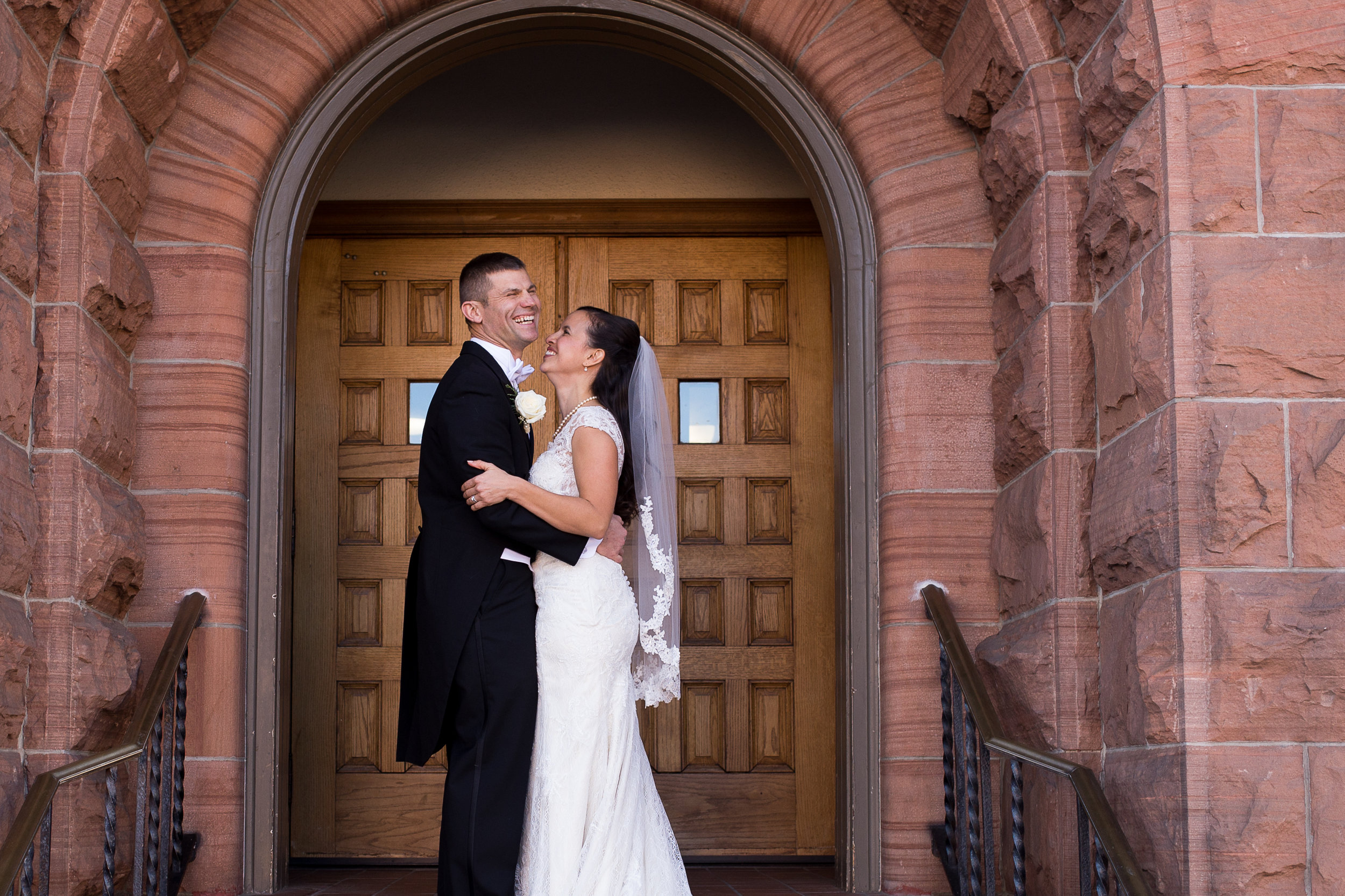 Couple facing each other and laughing while they embrace in front of a door at the First Baptist Church in downtown Colorado Springs Stacy Carosa Photography Intimate Wedding Photography
