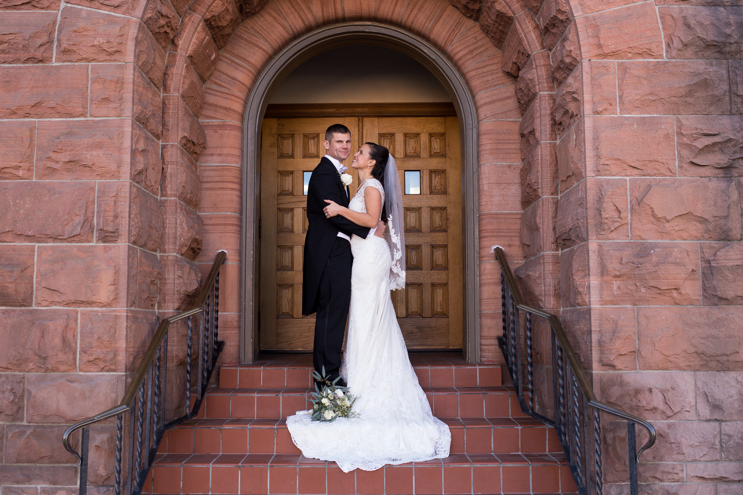 In the arc doorway of the First Baptist Church in downtown Colorado Springs is a couple holding each other and smiling Stacy Carosa Photography