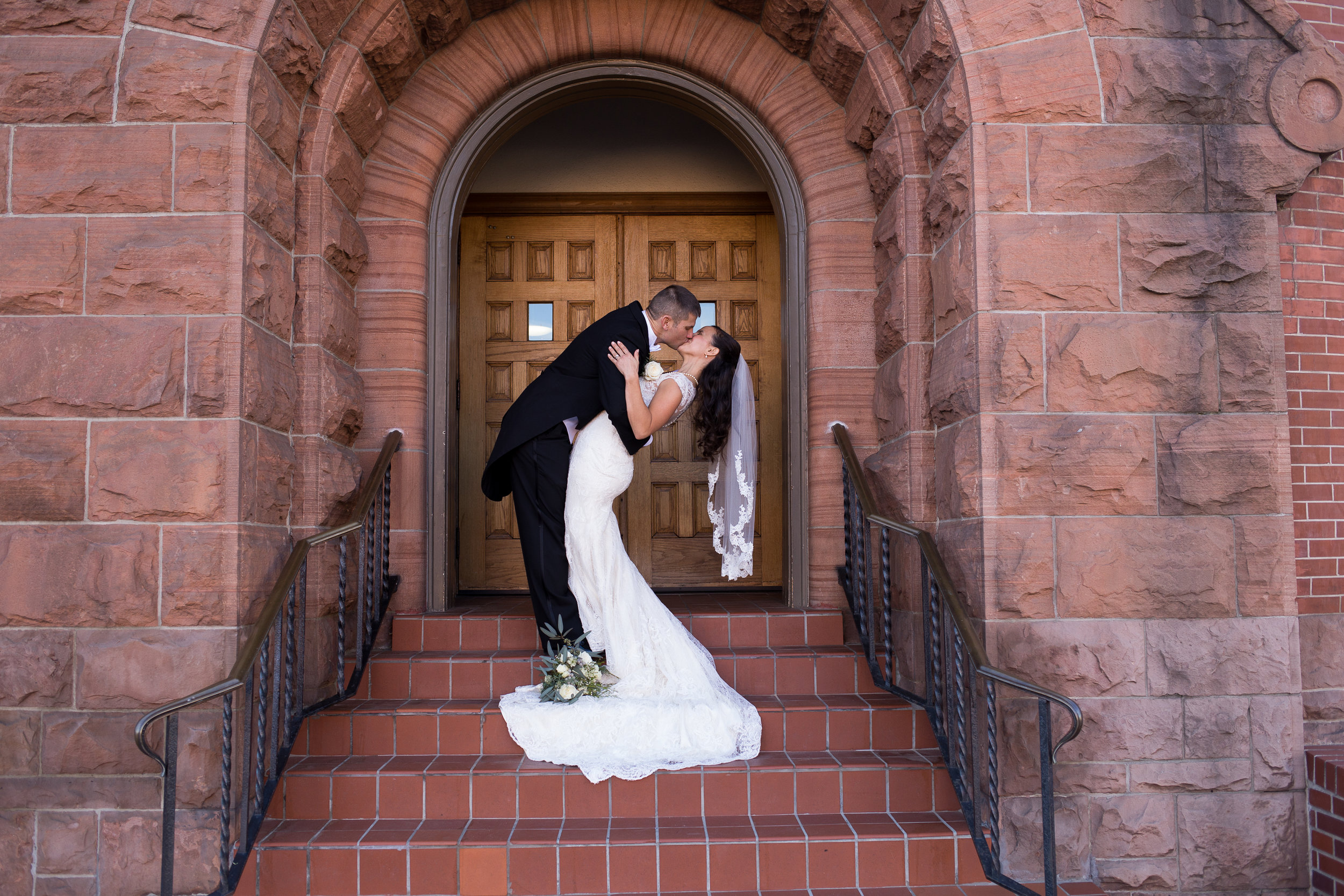 Bride being dipped and kissed in downtown Colorado Springs Winter Wedding at First Baptist Church Stacy Carosa Photography