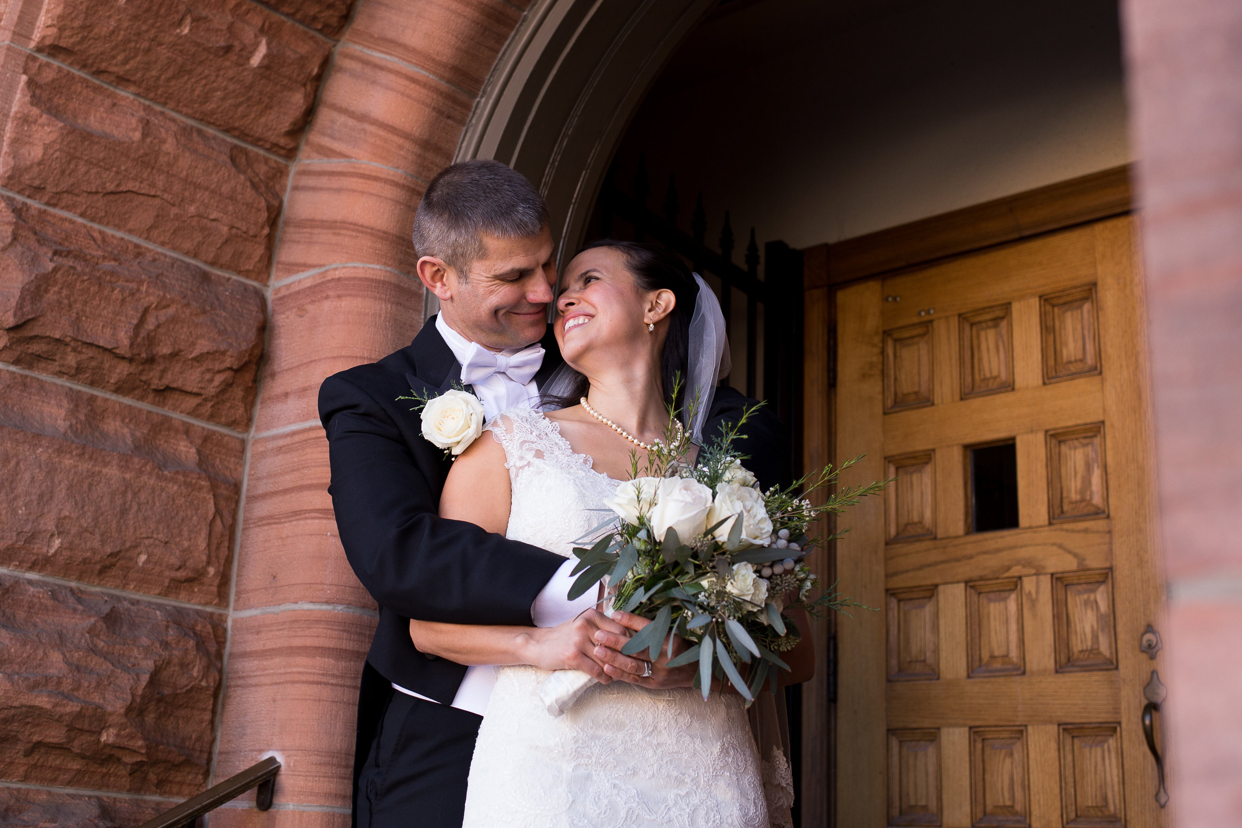 Groom hugging his bride around her shoulders while she leans back to look at him. Stacy Carosa Photography Colorado Springns Winter Wedding at First Baptist Church