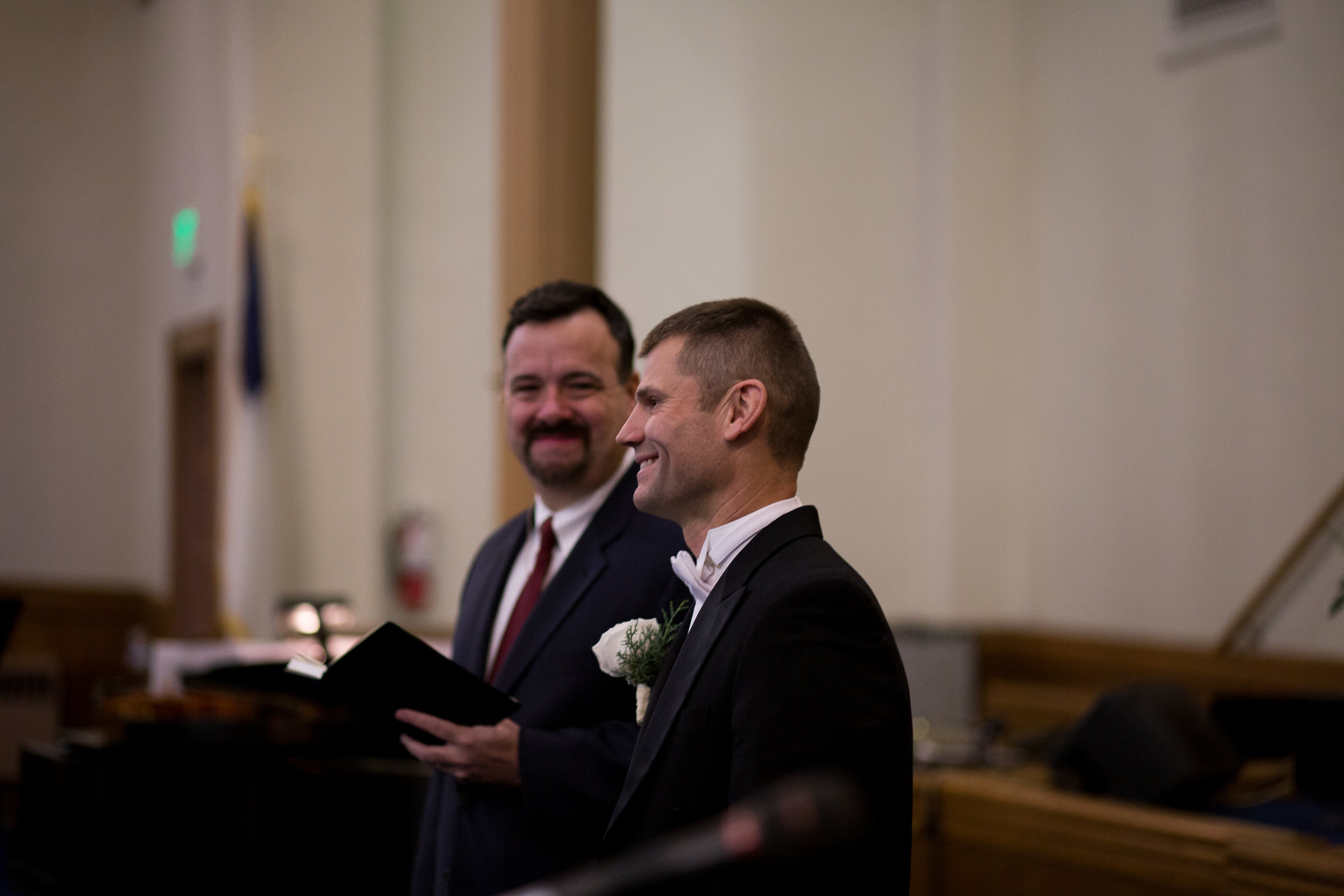 Groom smiles as a watches his bride walk down aisle at First Baptist Church wedding in Colorado Springs Stacy Carosa Photography
