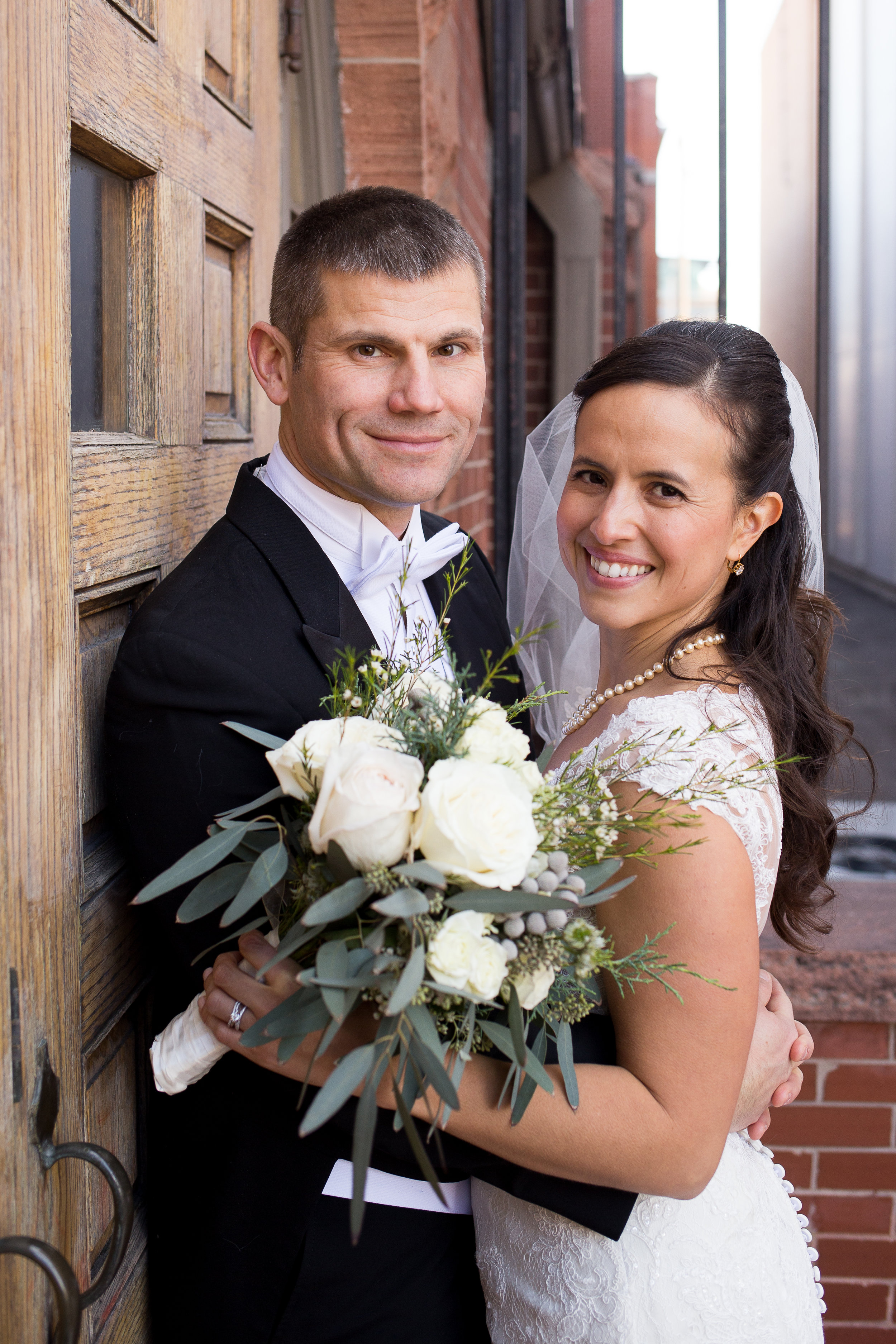 Winter Wedding at First Baptist Church outside by the brick wall in Colorado Springs Stacy Carosa Photography