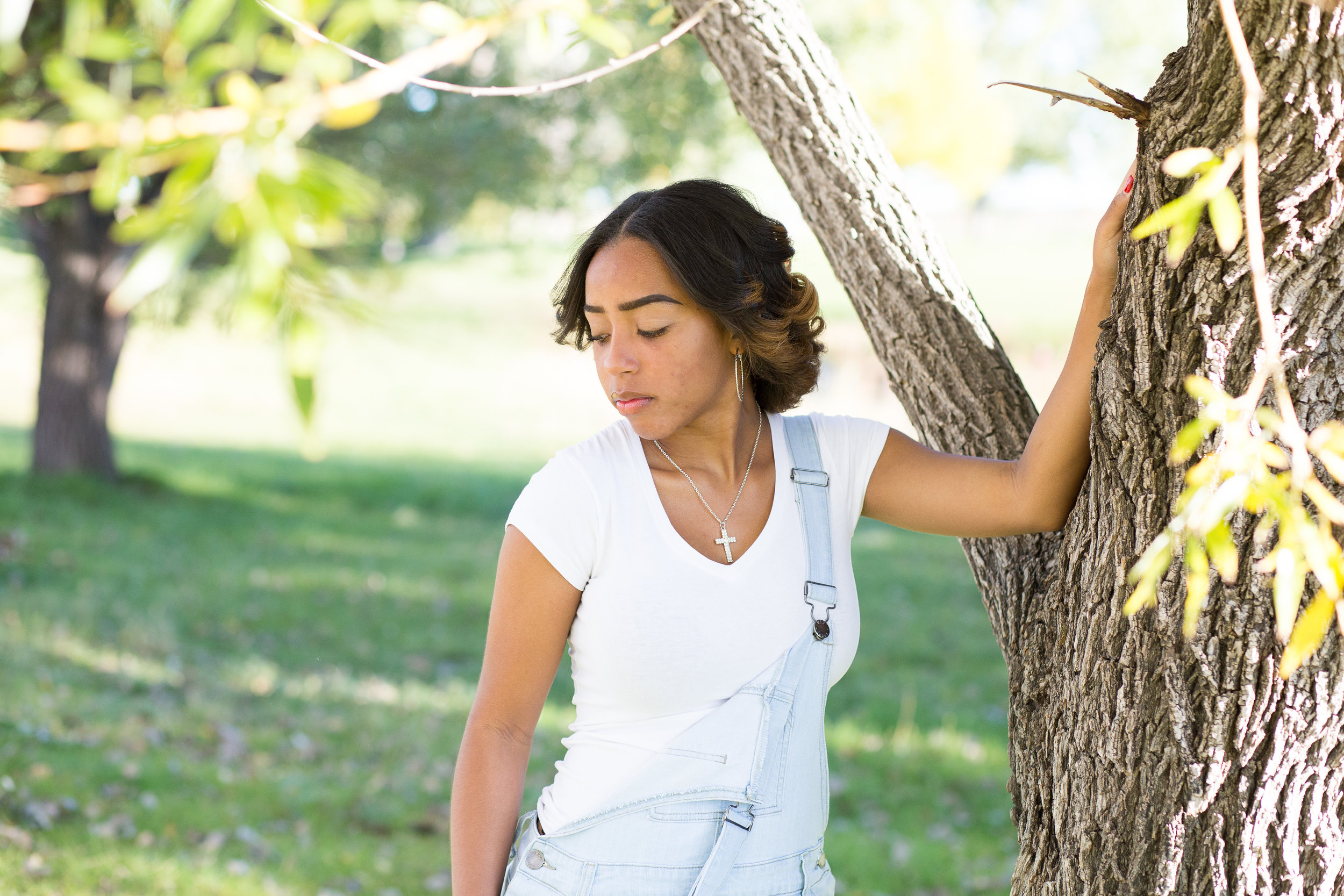 Widefield High School in Colorado Springs Senior Photographer Girl holding on to side of tree and looking at ground in deep thought Stacy Carosa Photography