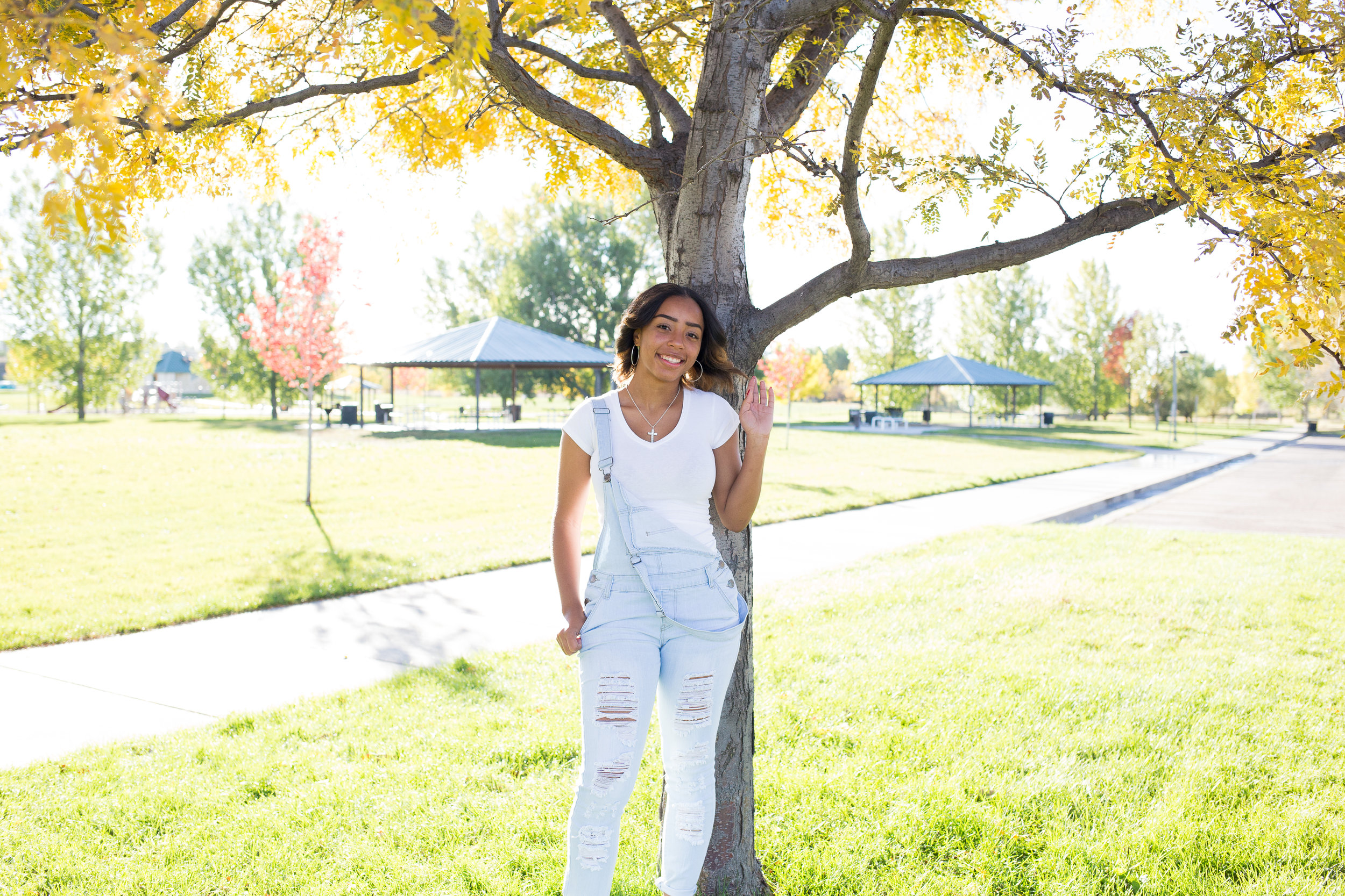 Widefield High School girl in overalls leaning again a tree with fall colors for her senior photos at Fountain Creek Regional Park in Colorado Springs, CO Stacy Carosa Photography