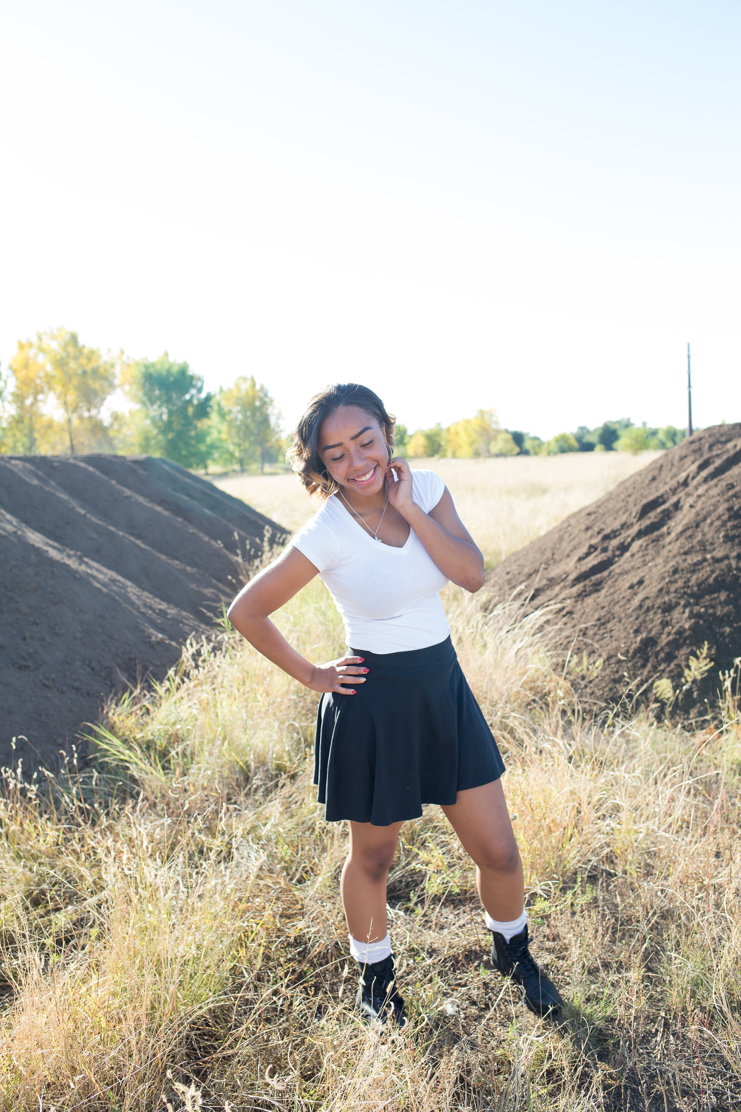 Widefield High School senior girl standing with hand on hip looking at the ground laughing for senior photos at Fountain Creek Regional Park in Colorado Springs, CO Stacy Carosa Photography