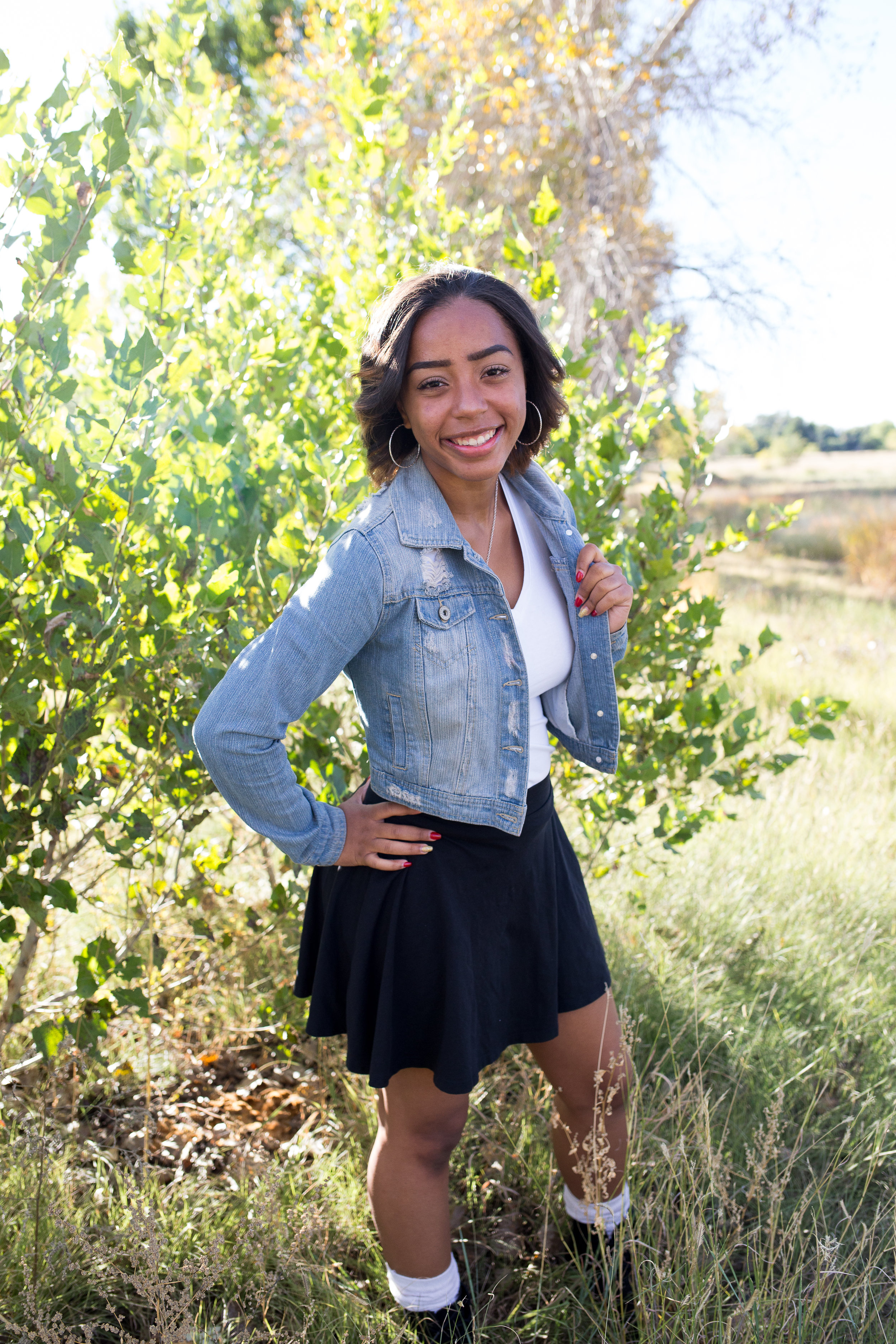 Girl in jean jacket standing among the green trees at Fountain Creek Regional Park in Colorado Springs, CO for senior photos Stacy Carosa Photography