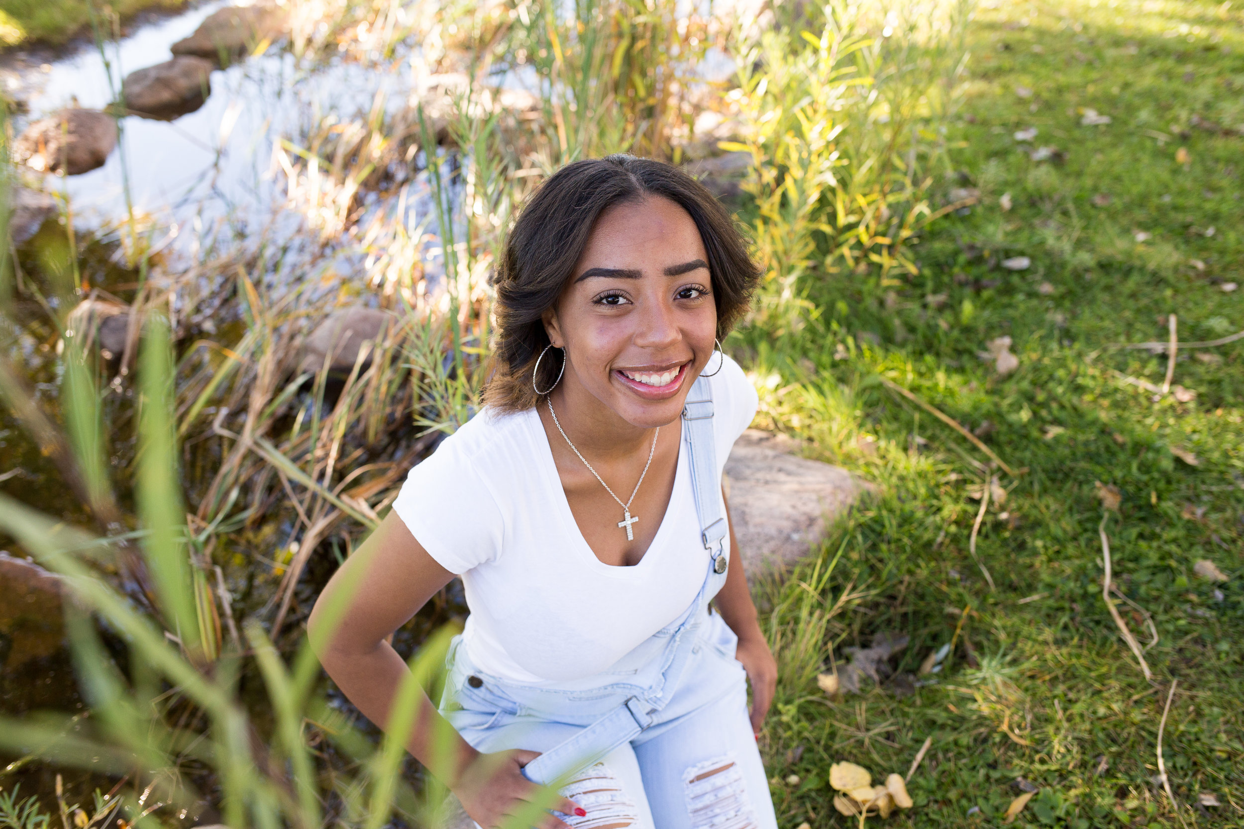 Colorado Springs Senior Photography at Fountain Creek Regional Park Girl sitting by river and tall grasses smiling at camera Stacy Carosa Photography