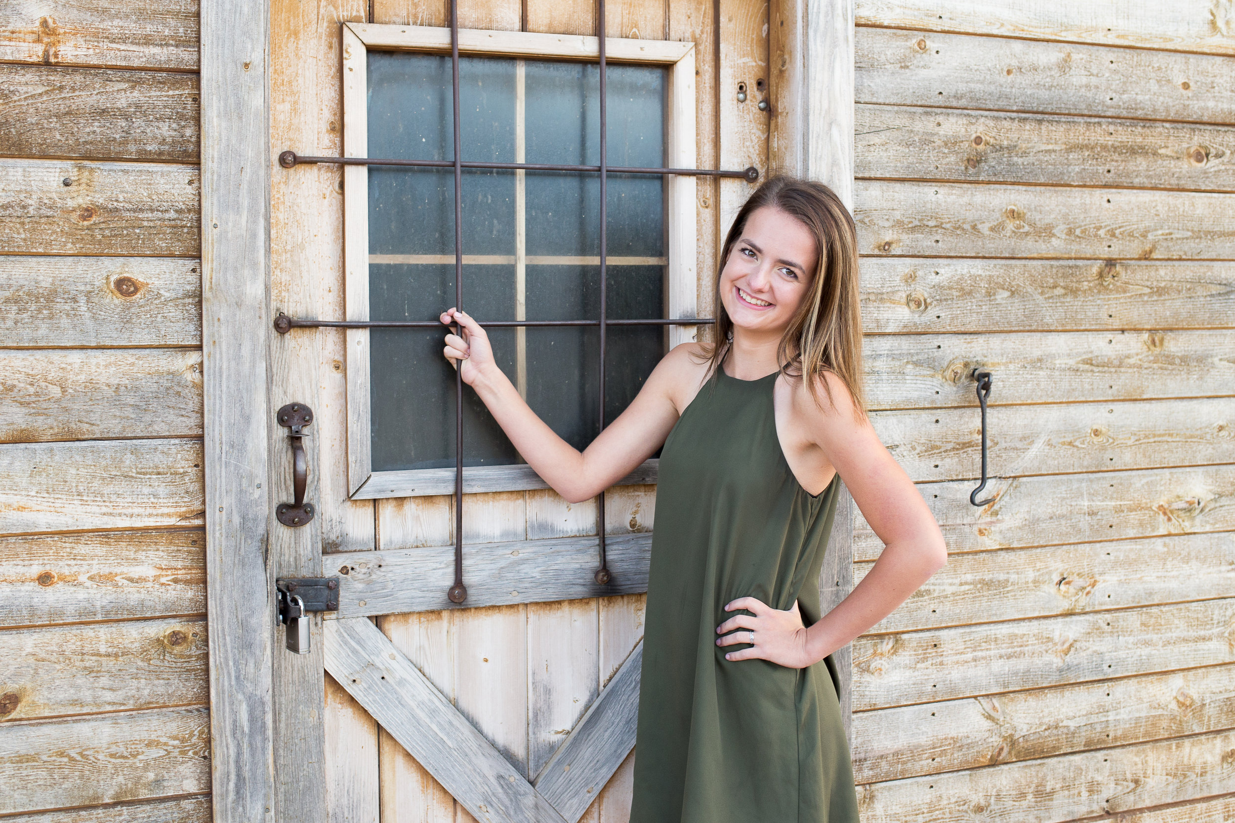 Rock Ledge Ranch Senior Photos girls standing by barn door holding on to the window bars and smiling at camera Stacy Carosa Photography Colorado Springs