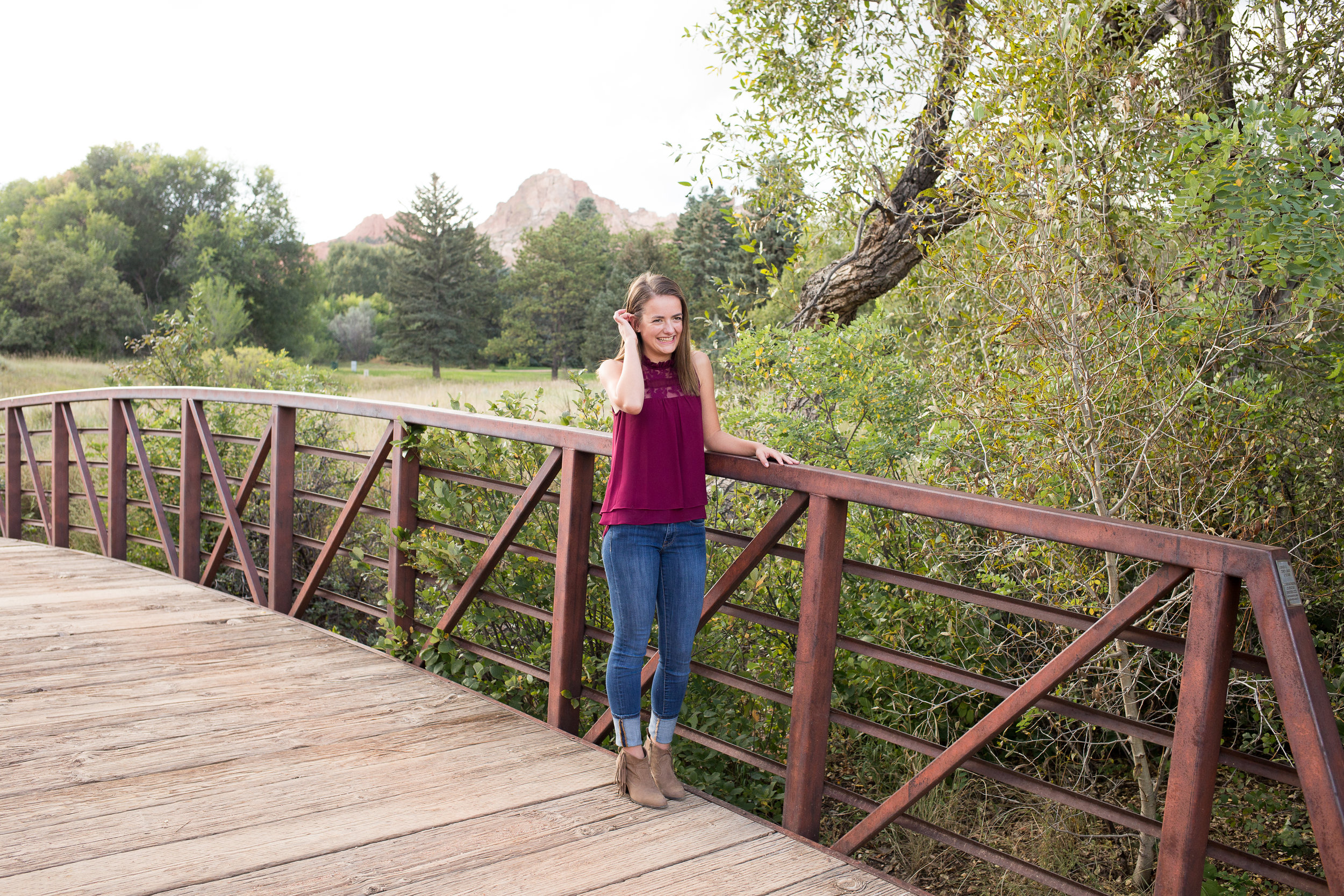 Girl standing on bridge at Rock Ledge Ranch in Colorado Springs for her senior photos laughing in the distance Stacy Carosa Photography Colorado  Springs Senior Photographer Denver Senior Photographer