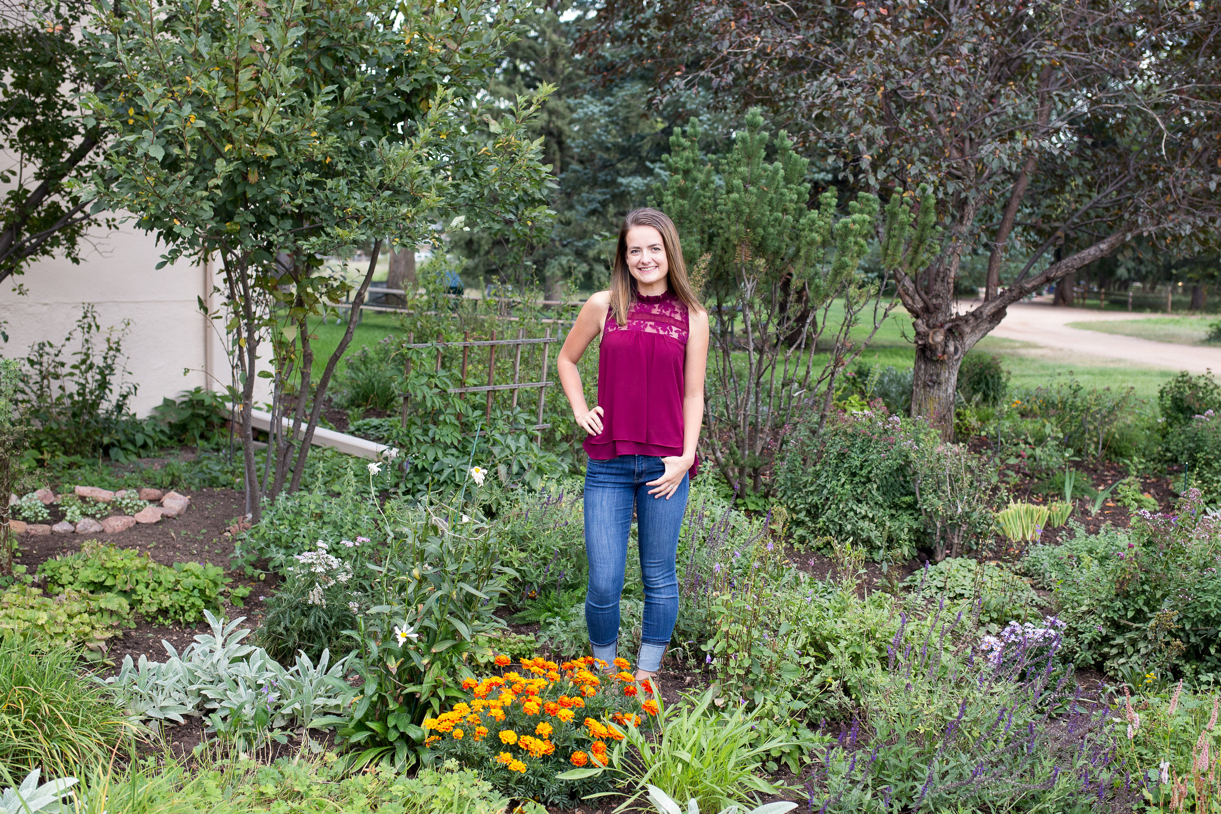Standing among the fall flowers with hand in her pocket for a senior photo session Rock Ledge Ranch Senior Photography Session in Colorado Springs Stacy Carosa Photography