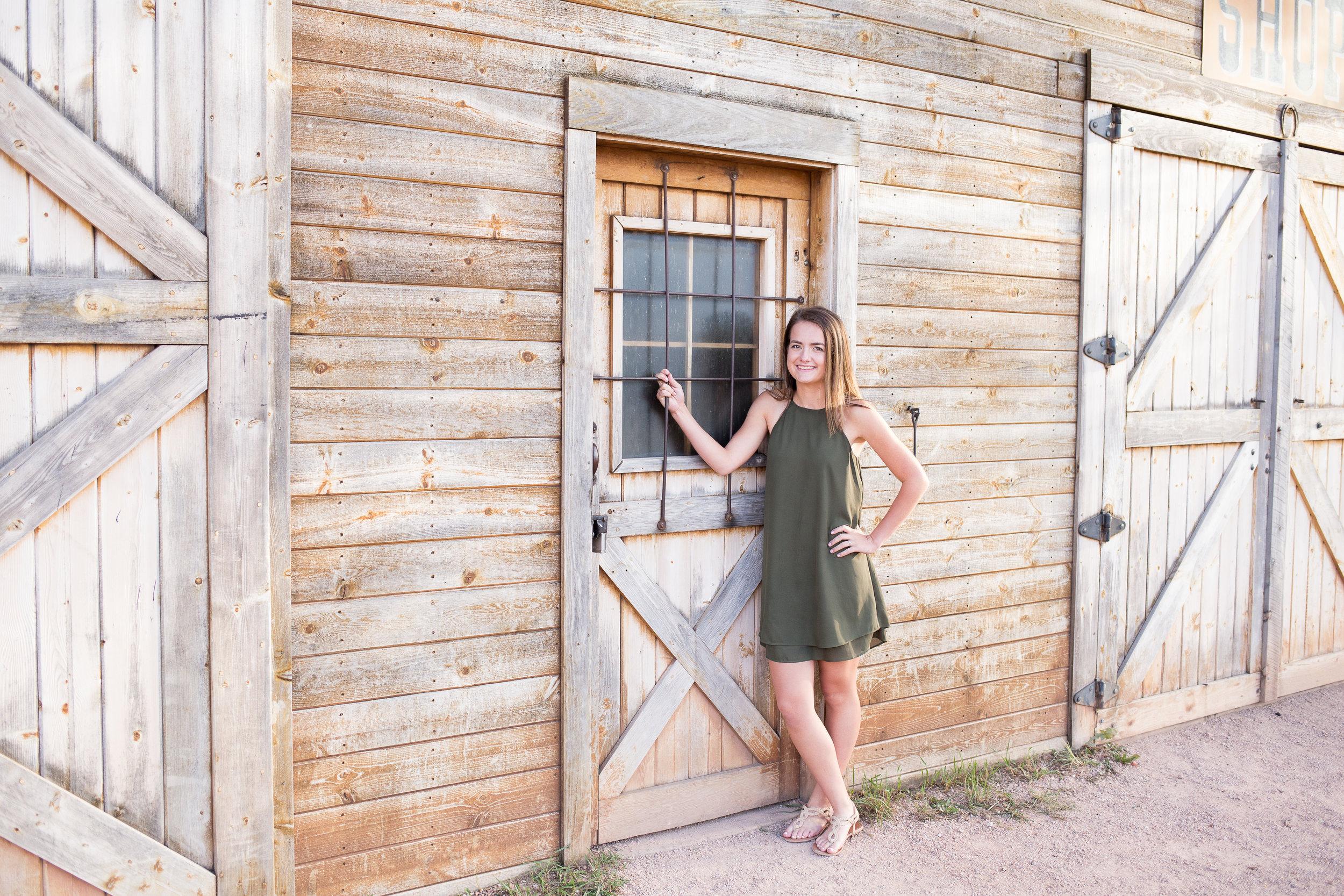 Rampart High School senior leaning against barn door for her Colorado Springs Senior session at Rock  Ledge  Ranch | Stacy Carosa Photography  Denver Senior Photographer