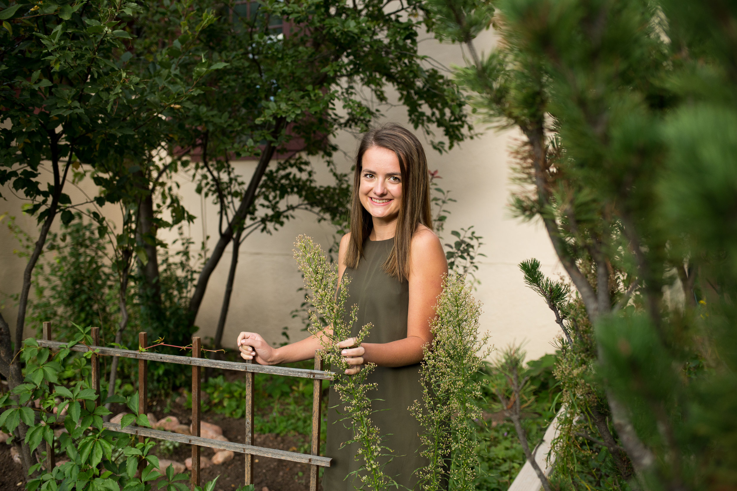 Girl standing among tall green plants in Rock Ledge Ranch for her Colorado Springs Senior Photography Session Stacy Carosa Photography