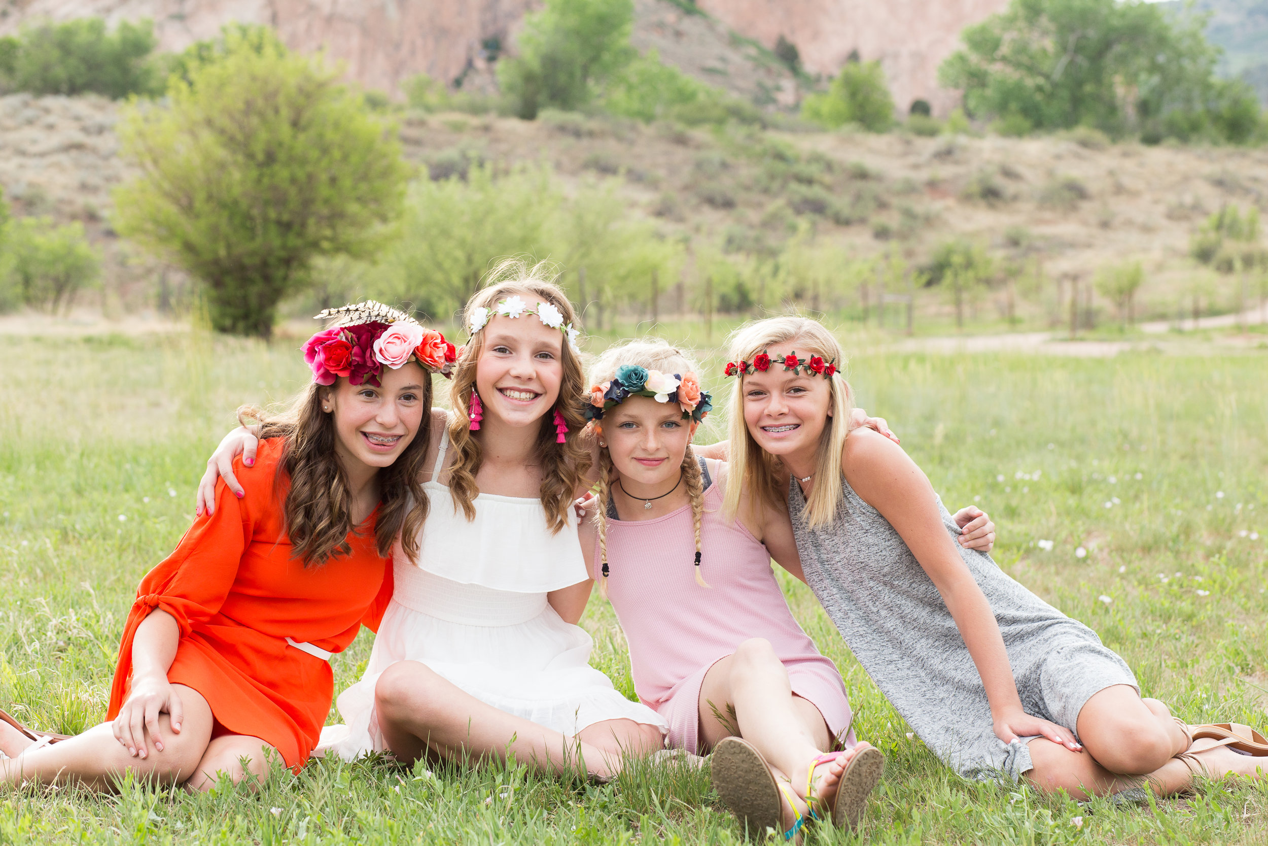 Colorado Springs Senior and Tween Photographer | Colorado  Springs Tween and Senior Photography | Stacy Carosa Photography | Middle school friends sitting in field with floral crowns and smiling at camera