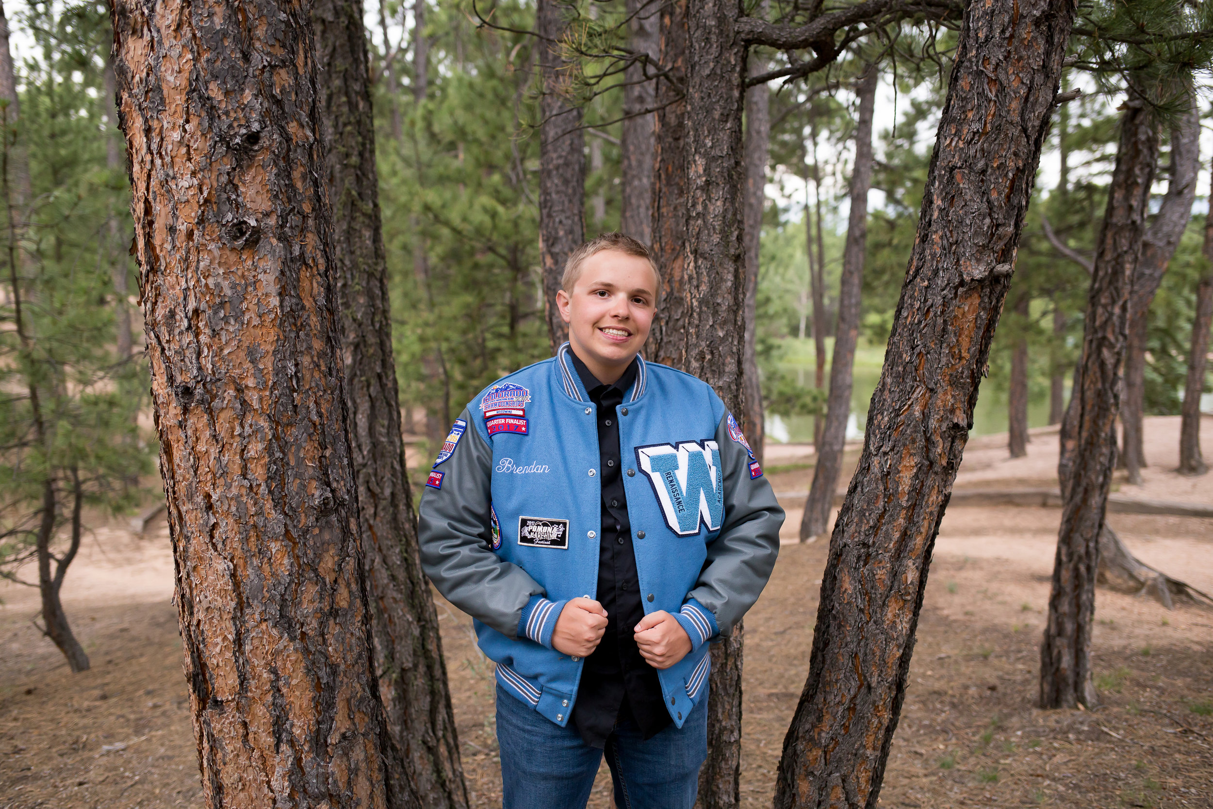 Colorado Springs Senior Photography | Stacy Carosa Photography | Colorado Springs senior photographer | senior session at Fox Run Park | Widefield high school senior among pine trees varsity jacket