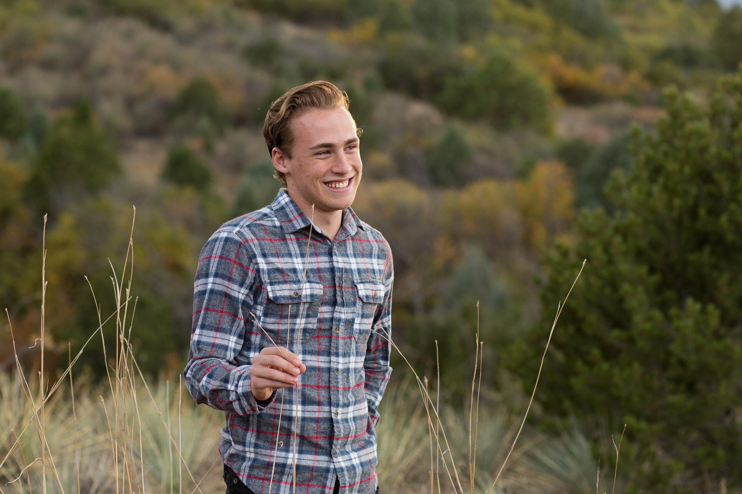 Senior boy from Palmer High School standing in field | Colorado Springs Senior Photography | Colorado Springs Senior Photographer | Stacy Carosa Photography | Colorado Senior Portraits | Doherty High School