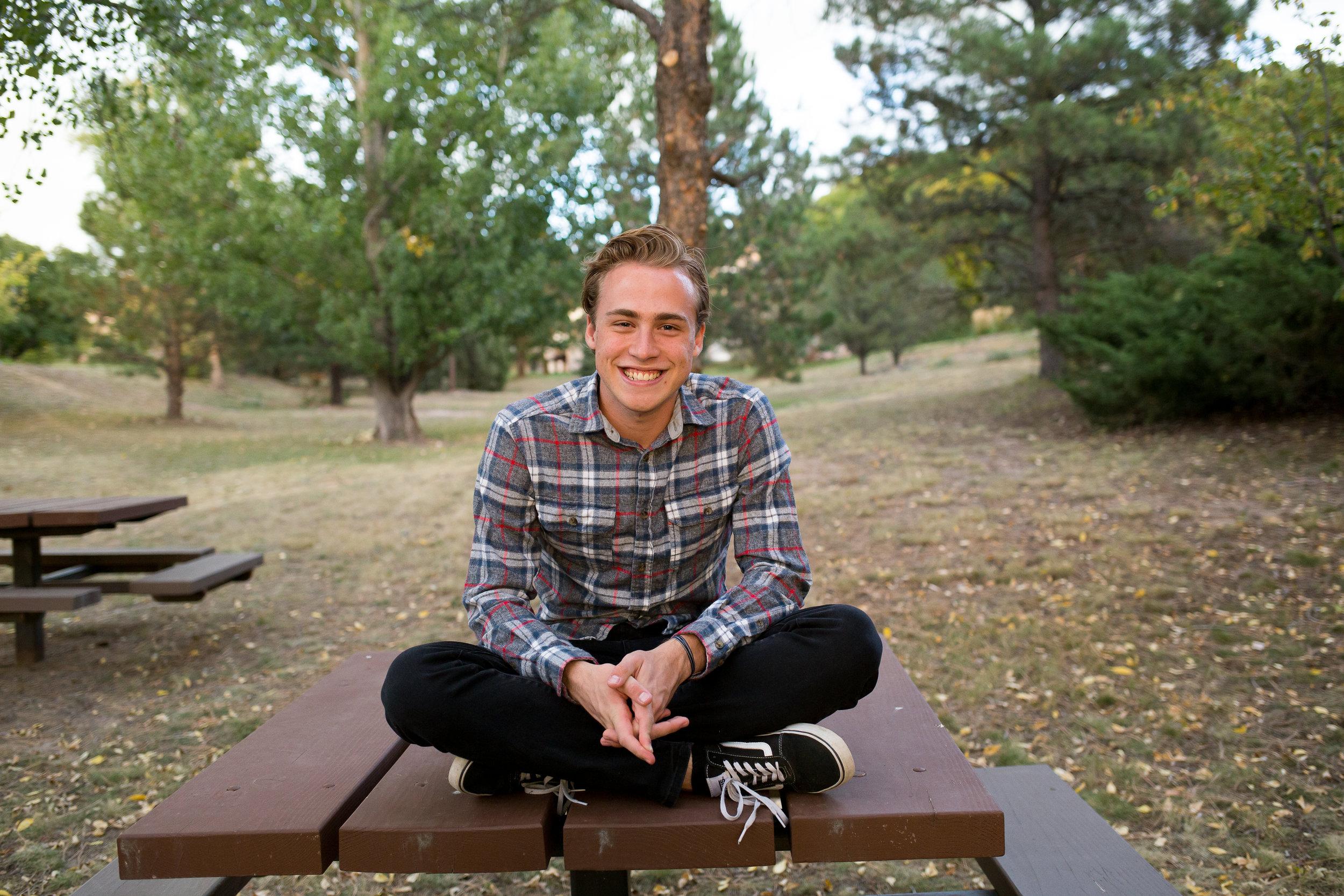 Senior boy sitting in park | Colorado Springs Senior Photography | Colorado Springs Senior Photographer | Stacy Carosa Photography | Colorado Senior Portraits | Doherty High School