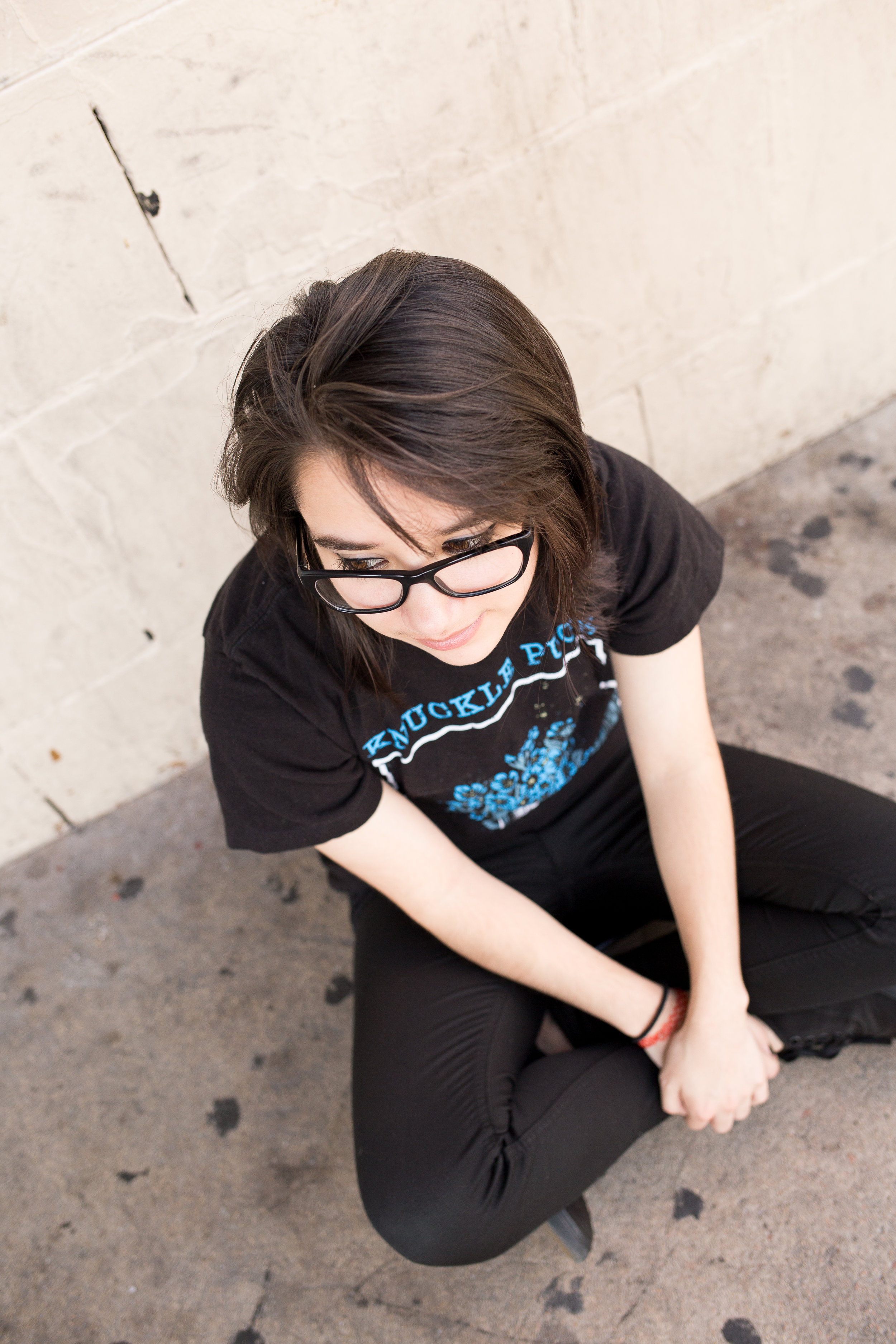 Colorado Springs Senior Photography | Colorado Springs Senior Photographer | Denver Senior Photographer | Girl with glasses sitting on ground by music venue | Stacy Carosa Photography