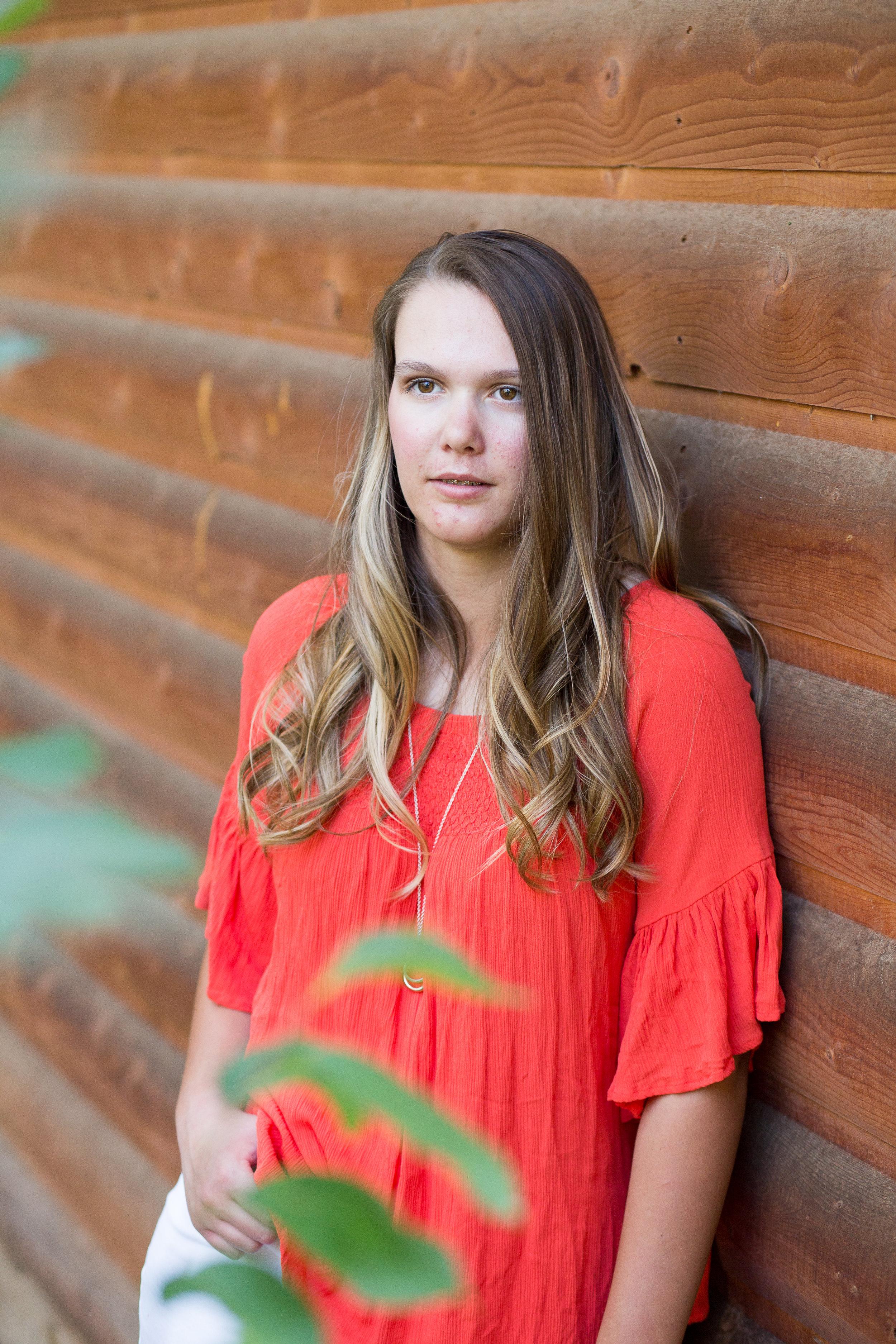 Colorado Springs Senior Photographer   Colorado Springs Senior Photography   Stacy Carosa Photography   Senior girl sitting among forest for portrait session