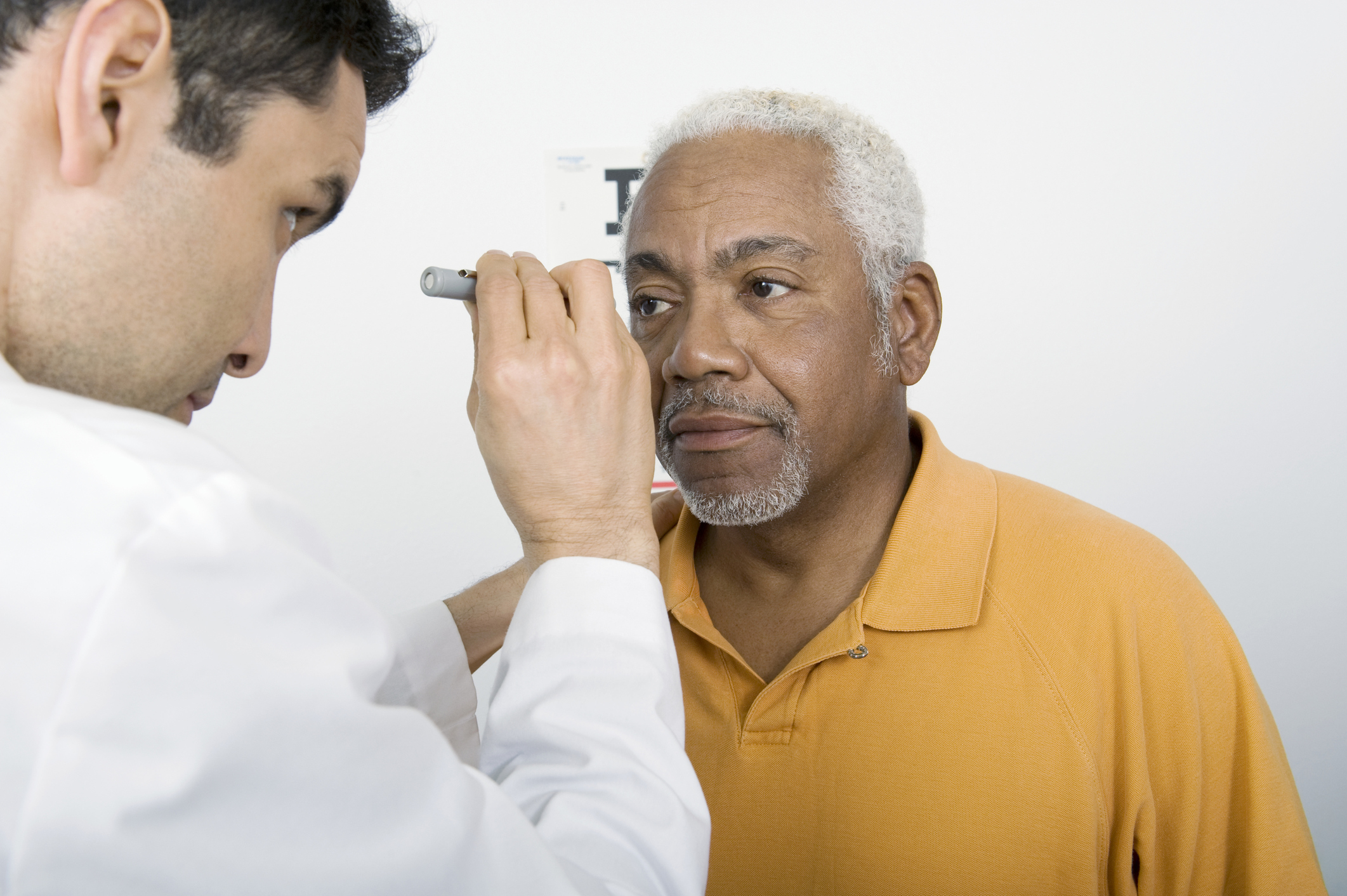 Checking pupils as part of an eye health exam.