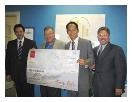 Jack Toan from Wells Fargo Bank presents a check for $100,000 for the technical assistant program 2008 - 2009 to the partnership between Small Business Financial Development Corporation of Orange County and Hispanic Business Consultants.  (From right to left)Eduardo Figueroa, Charles Ledgerwood, Jack Toan and Michael Ocasio