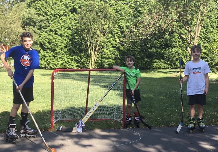 Protecting the goal as Hunter and Jack Galbavy play street hockey